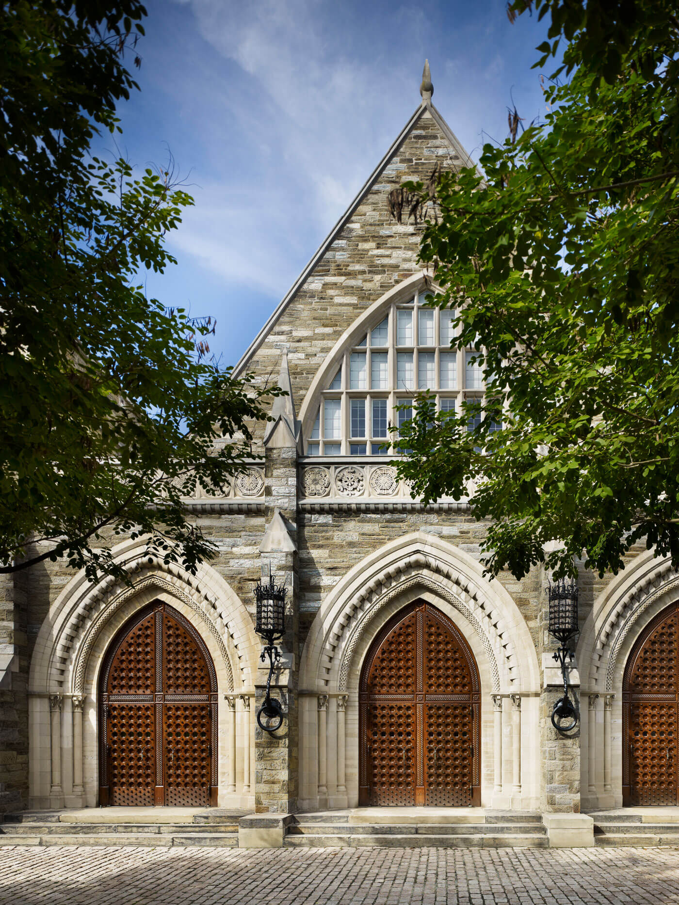 Historic entrance to Goodhart Hall with detailed, pointed stone arches and carved wooden doors.