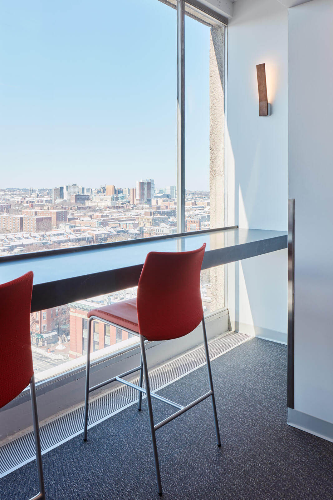 Red chairs at modern countertop overlook the Boston skyline from BU's Alumni Medical Library