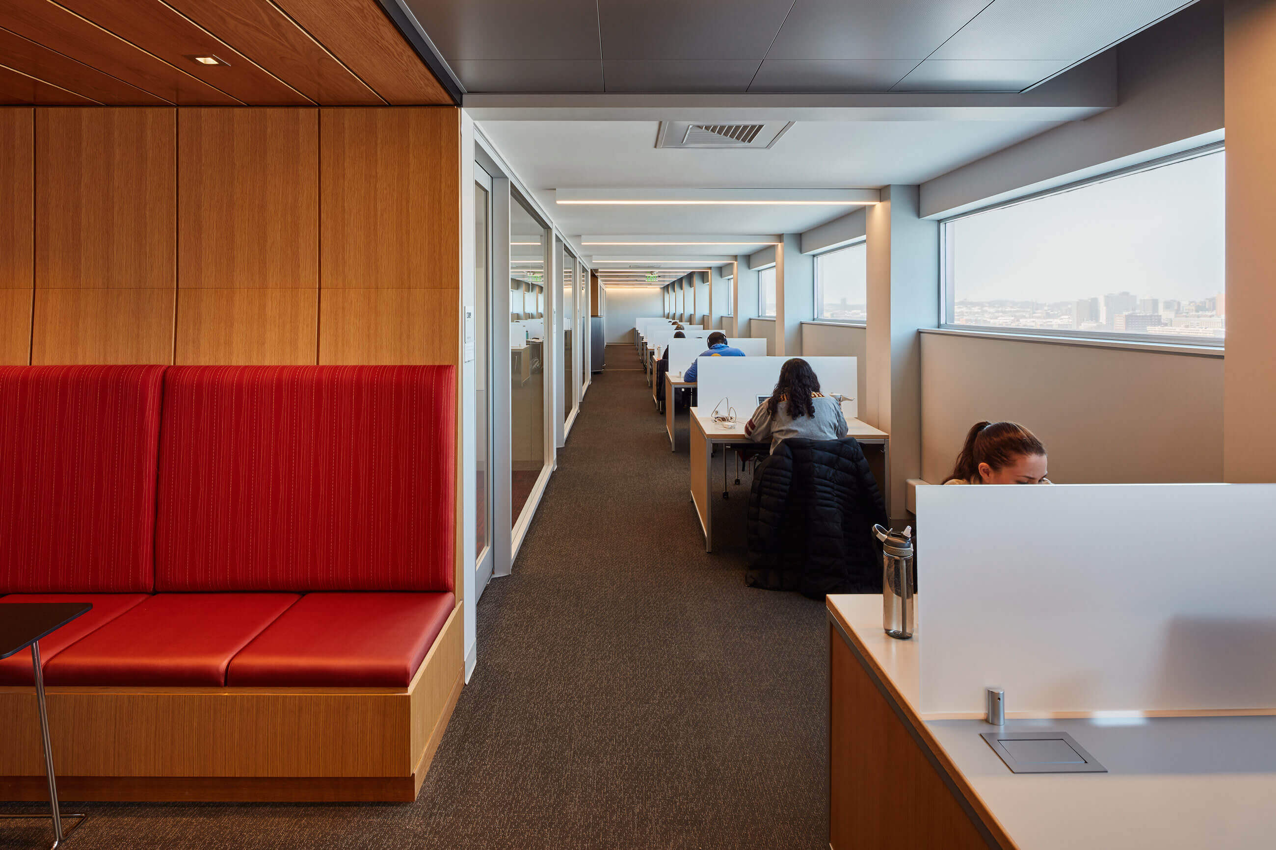 Finegold Alexander Architects installed warm wood finishes with red touches in this interior view of the library floor at BU's Alumni Medical Library