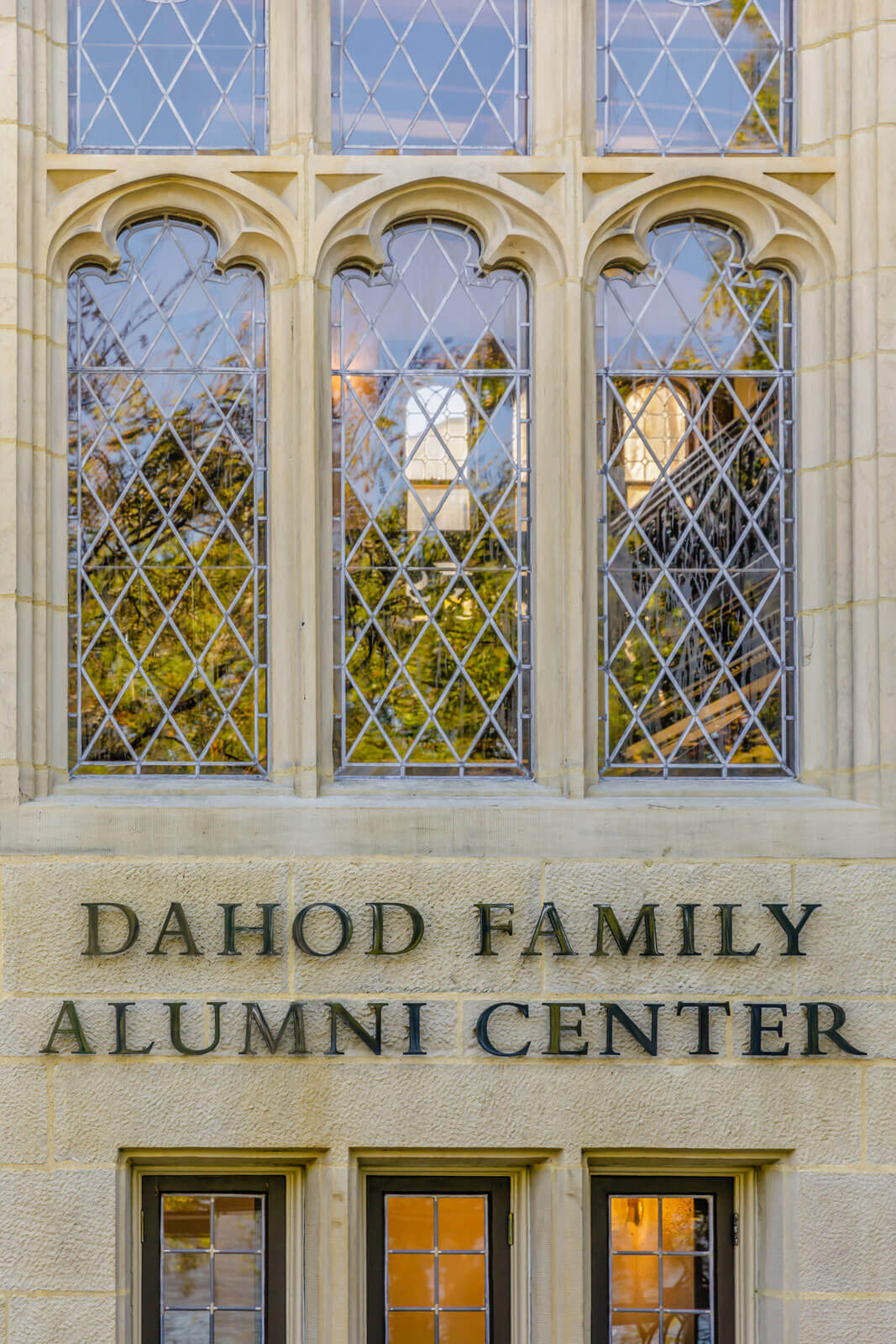 "Detail of carved stone widows over a sign that reads ""Dahod Family Alumni Center"" on the building's stone."