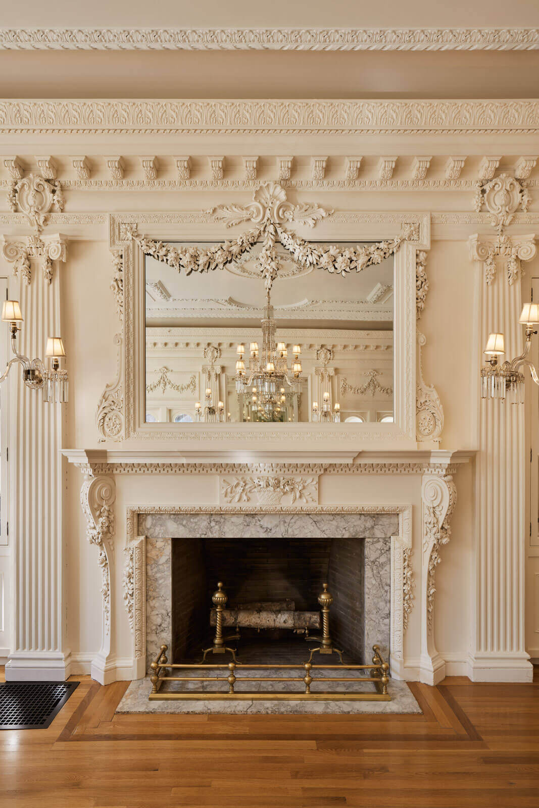 Elaborately restored fireplace with detailed moldings and light fixtures, with a mirror above it, reflecting the rest of the creme-colored room.
