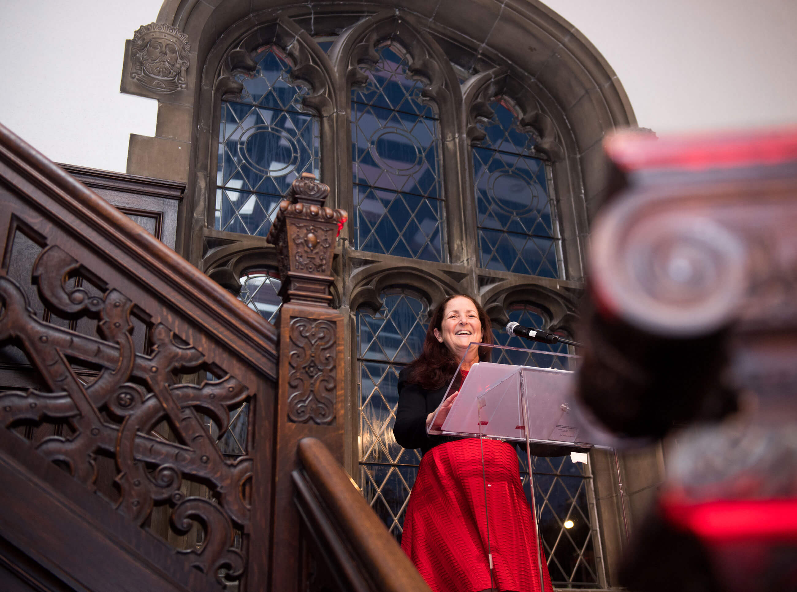 Image of a woman in a red dress speaking at a podium at a landing on a detailed wooden staircase, with historic windows in a stone arch behind her.