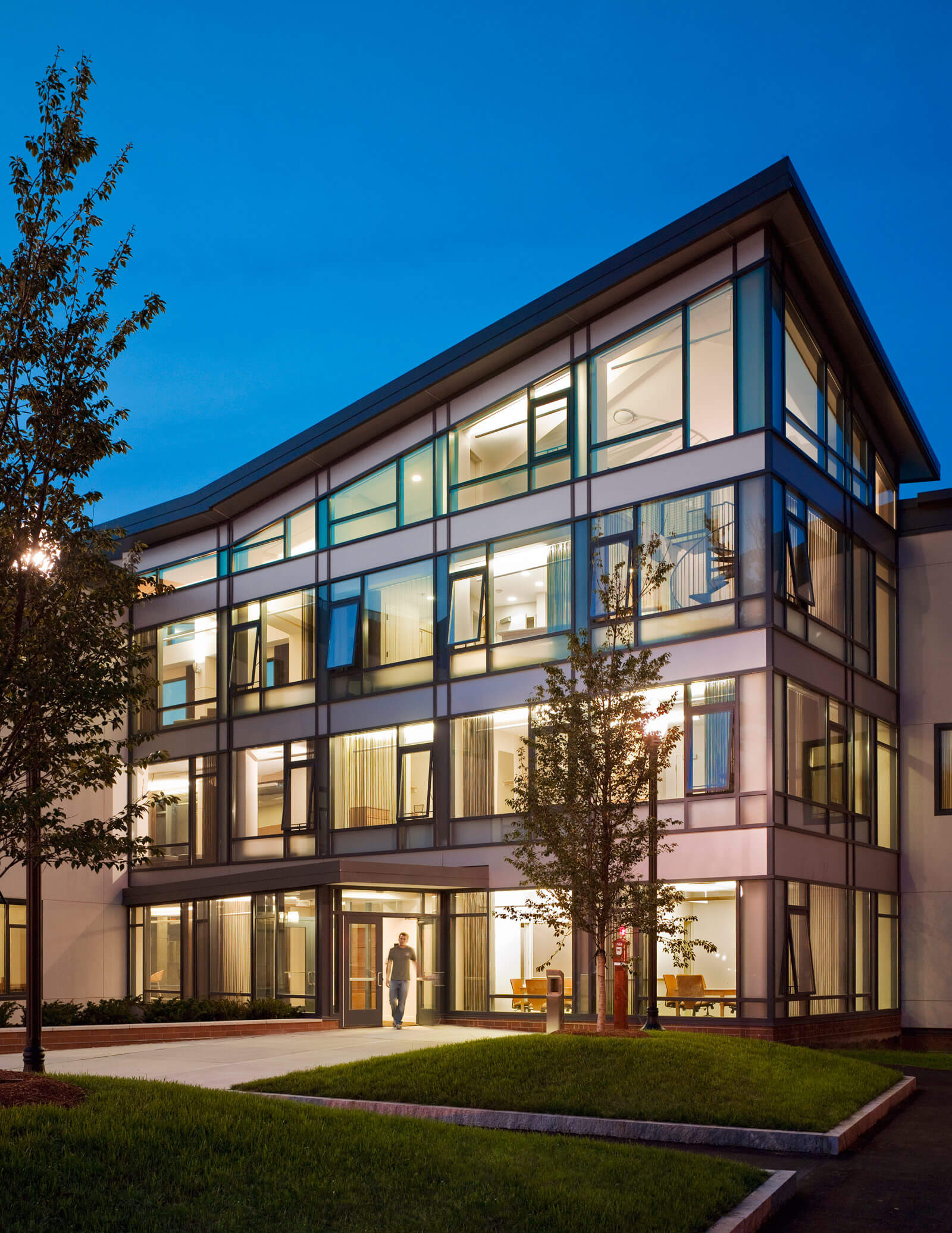 Modern dorm building with upward sloping roof, its large windows illuminated from the inside at dusk / night.