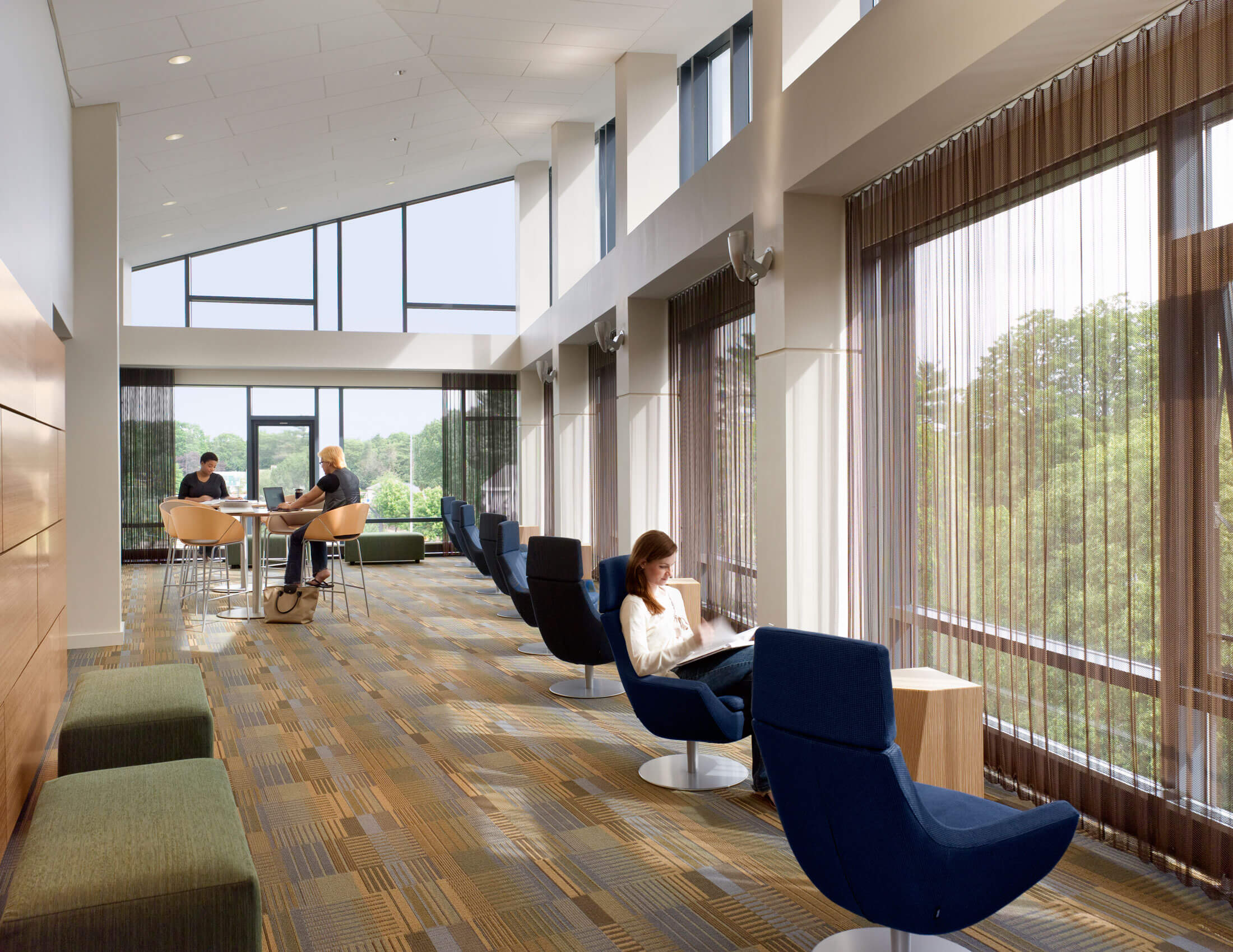 Students scattered in a variety of seating options to study or talk, in front of large windows under a sloping ceiling.