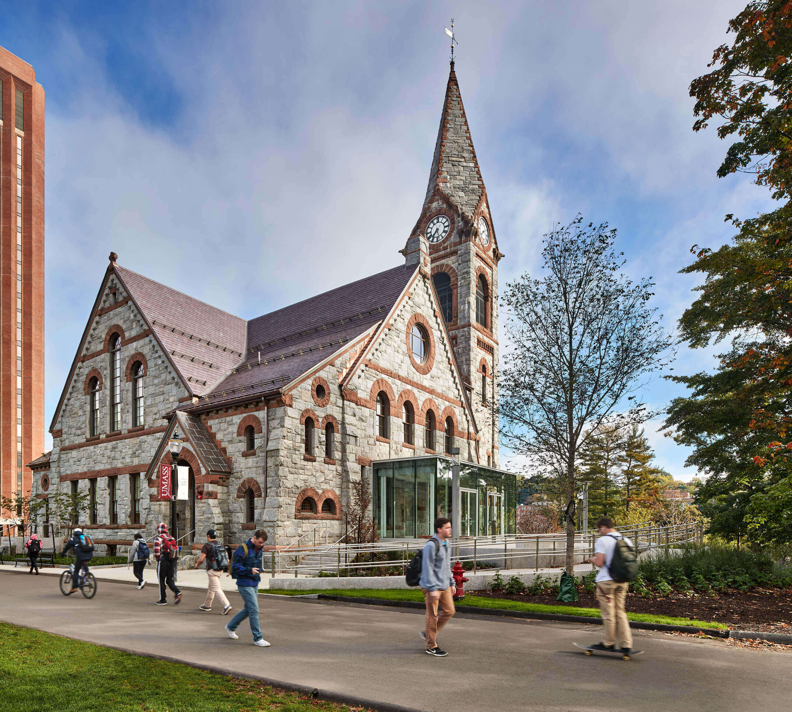 College students walking and skateboarding by new glass accessible entrance the UMass Amherst's Old Chapel.