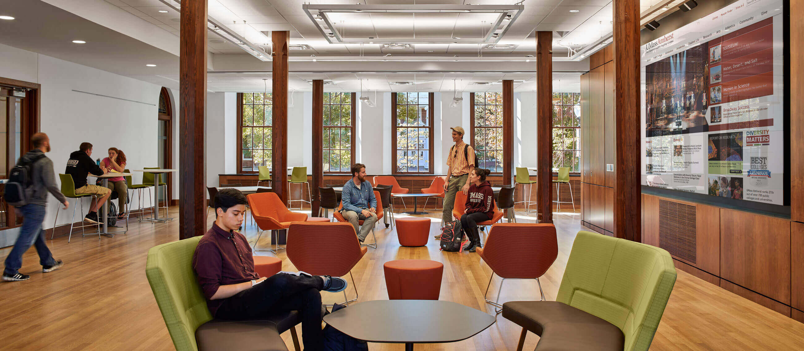 Students studying and socializing in lounge chairs and at tables in an open space with thin wooden columns and a large screen to the right.