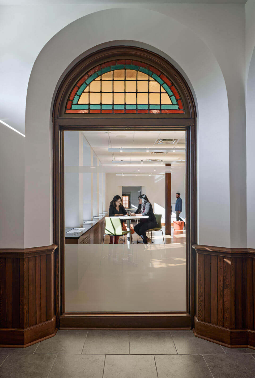 Two students studying, shot through an arched window with renovated glass detailing and wooden base-boards.
