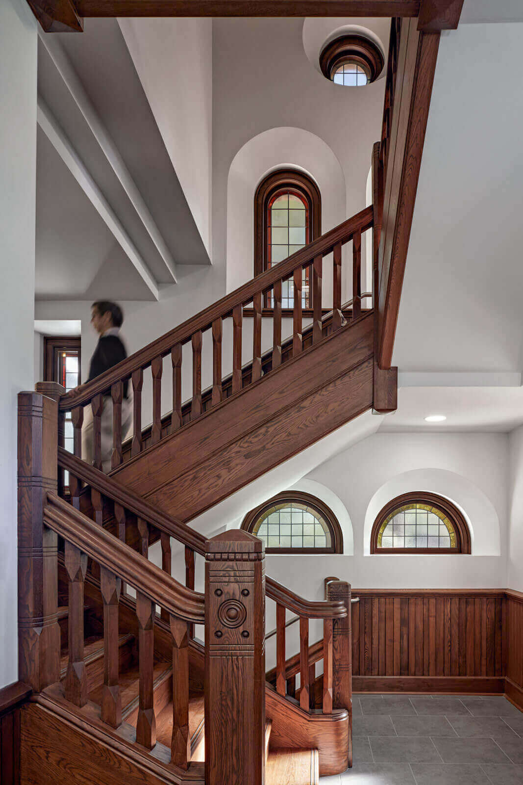 Student descending wooden staircase with multiple arched windows preserved in the background.