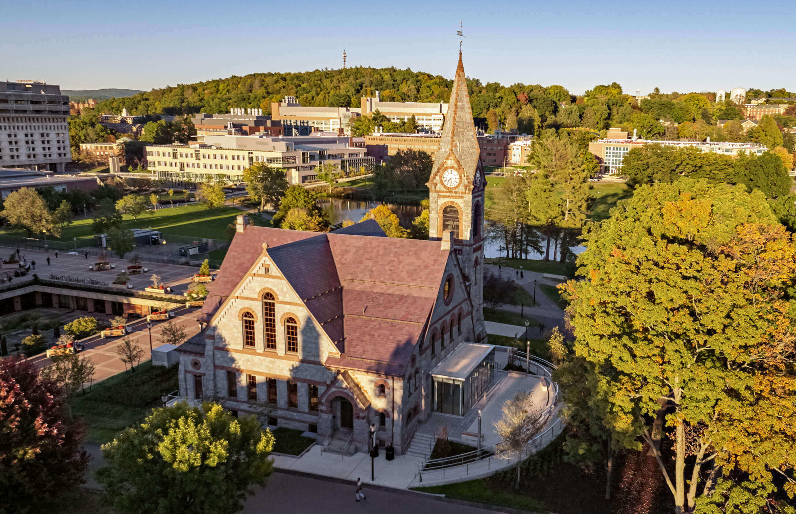 Drone shot of University of Massachusetts' Old Chapel in the summer, with the curved terrace providing access to the new glass entrance.
