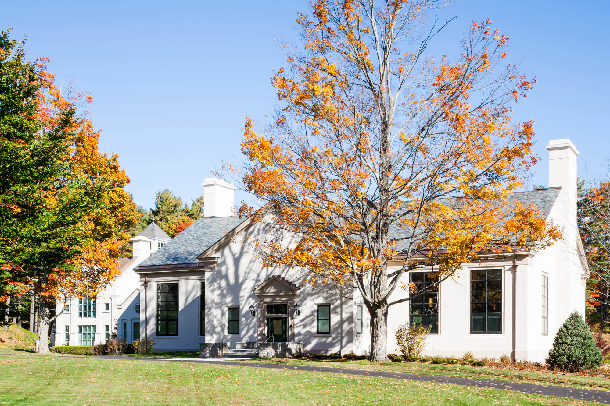 Exterior view of Geier Library at the Berkshire School, showing autumn leaves and blue sky