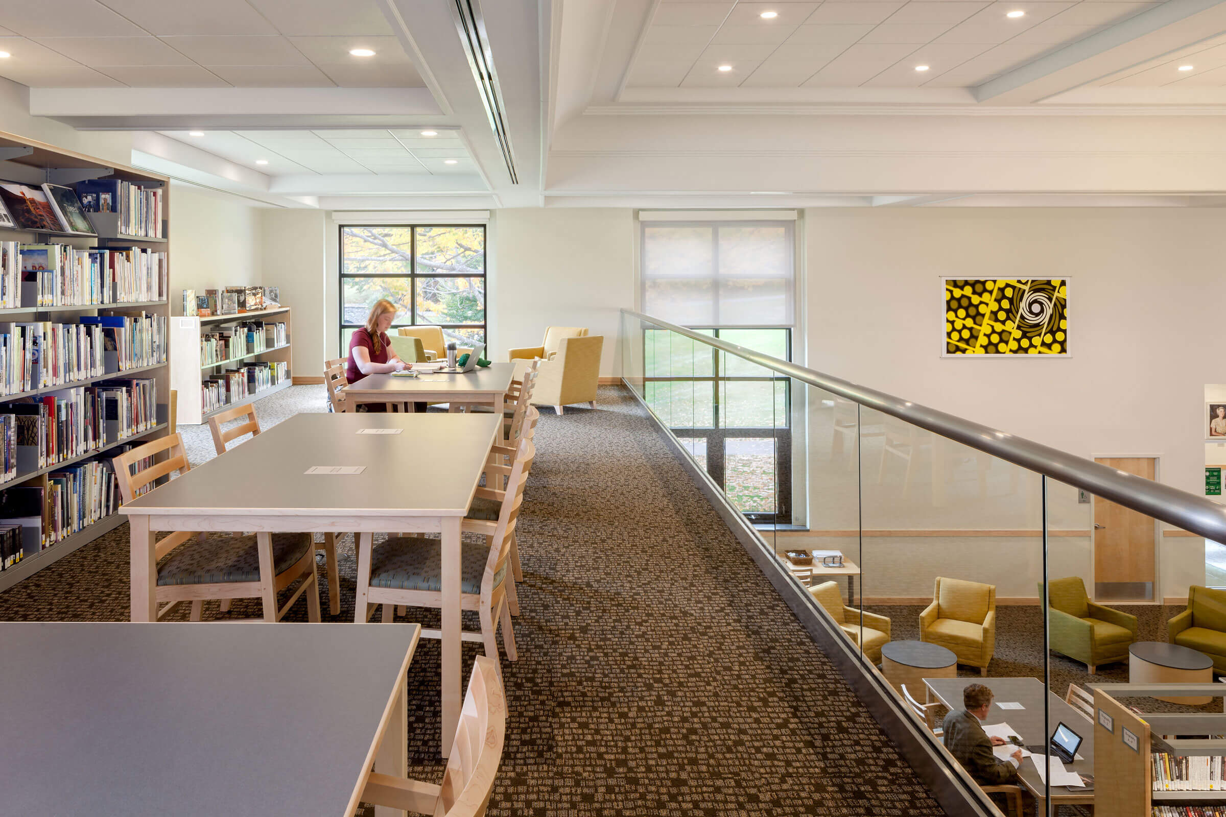 Upper balcony view of Geier Library, at the Berkshire School. Student artwork is seen on the walls, and the view down to the library's main floor.