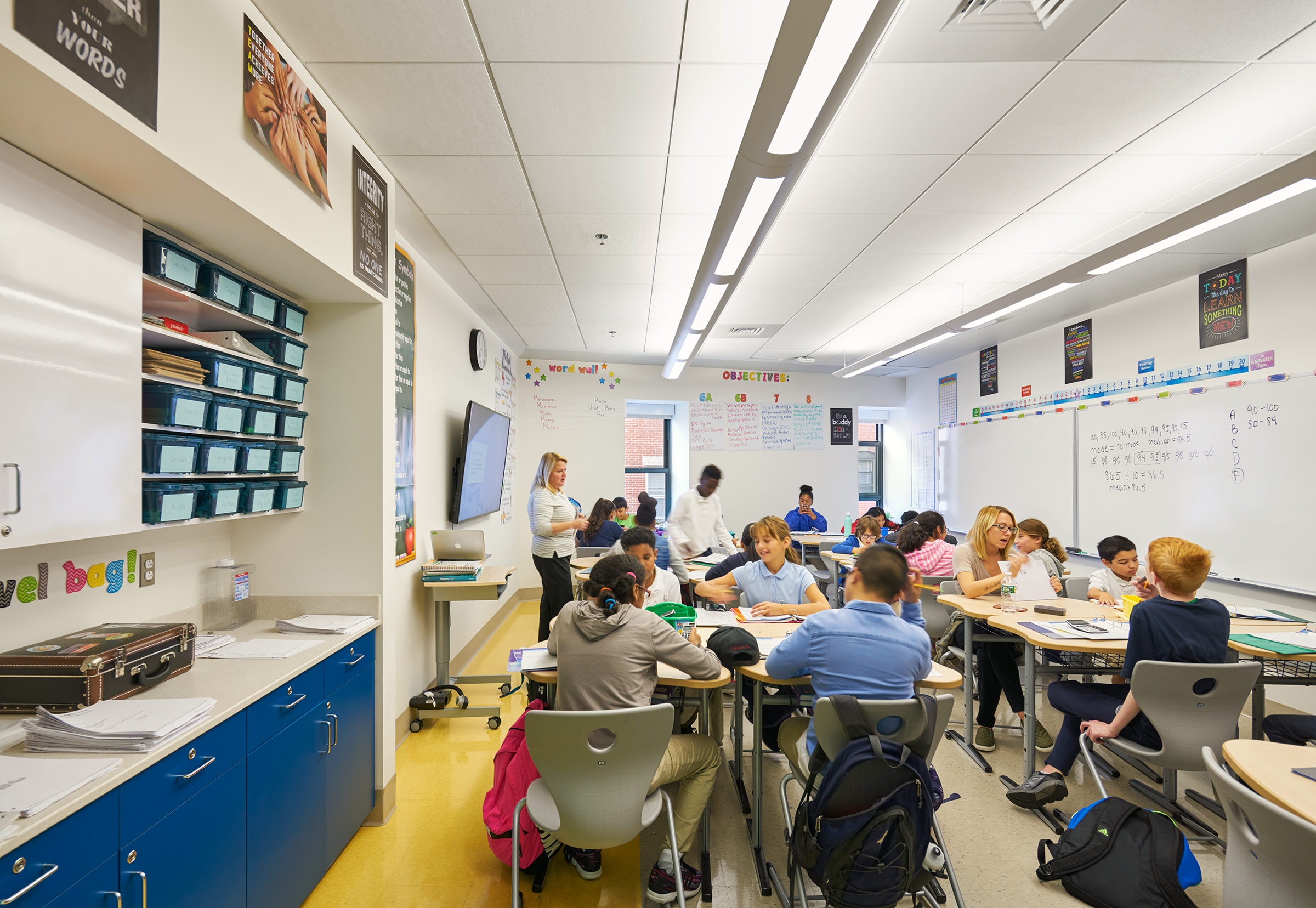 Students in a narrow, horizontal classroom with blue cabinets and and yellow floor.