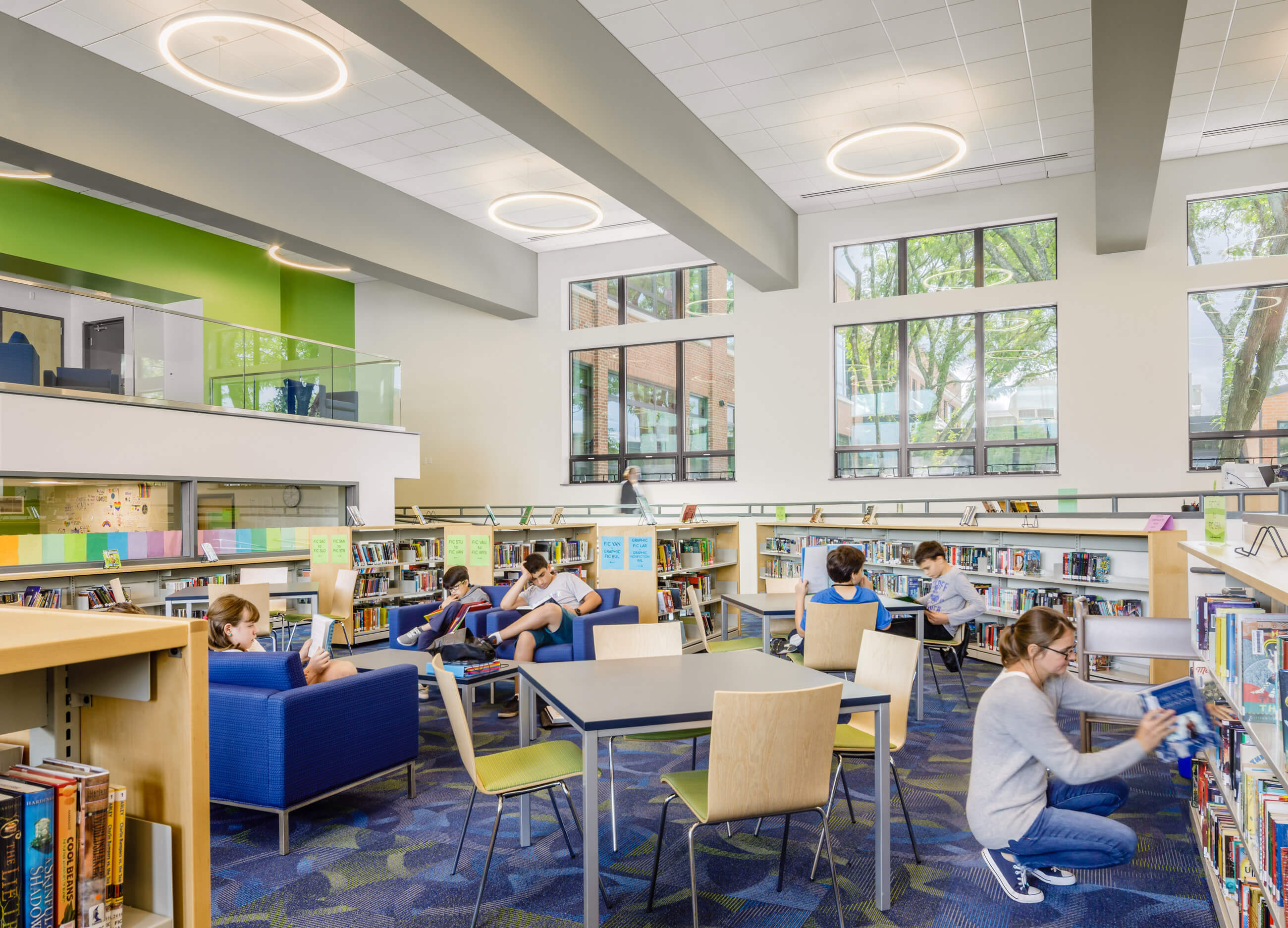 Students and teachers in different sitting areas of the media center, with bright daylight and blue and green colors.