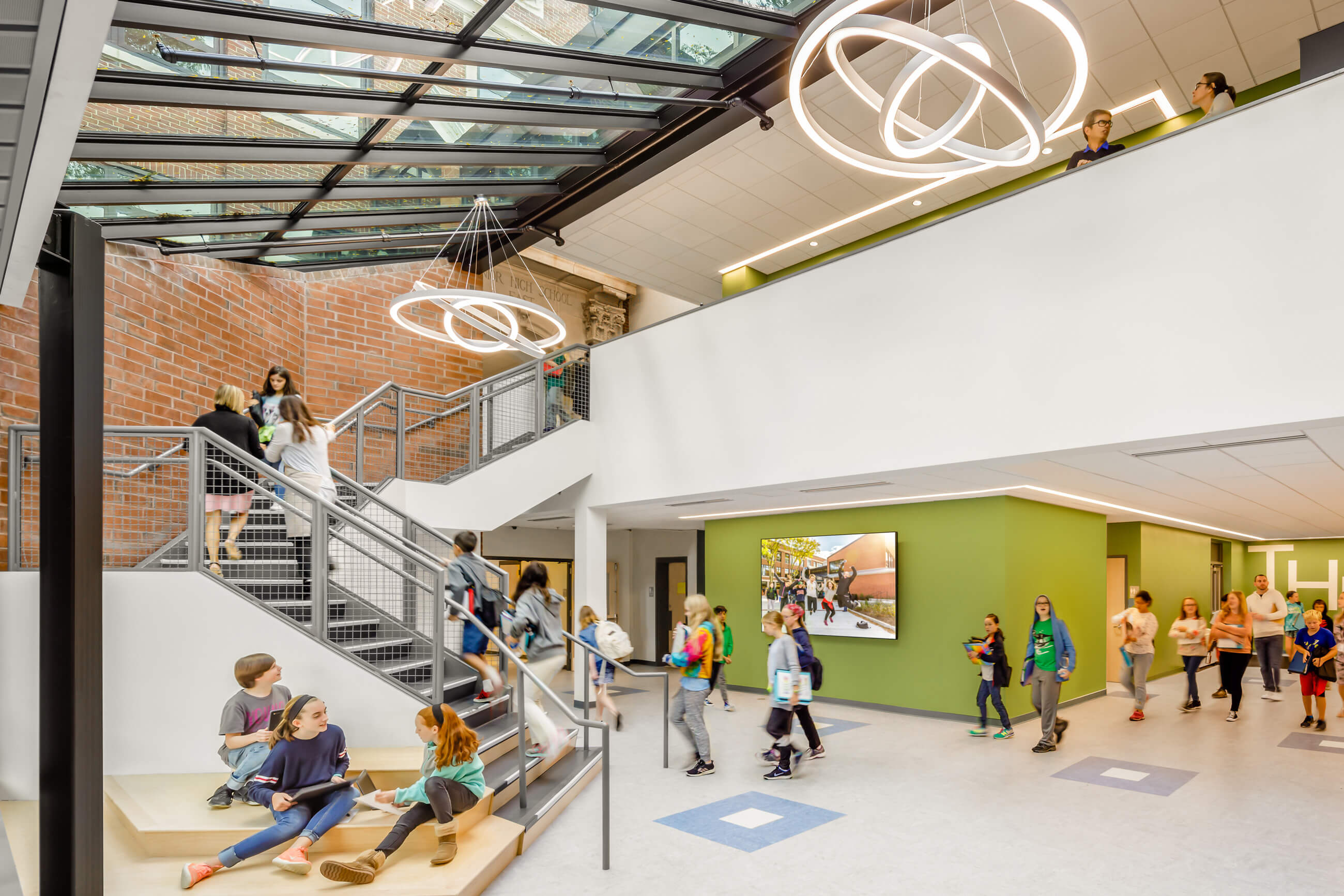 Students in the new entrance foyer, which features green and white walls, an existing brick wall, and a sky-light with modern circular lights.