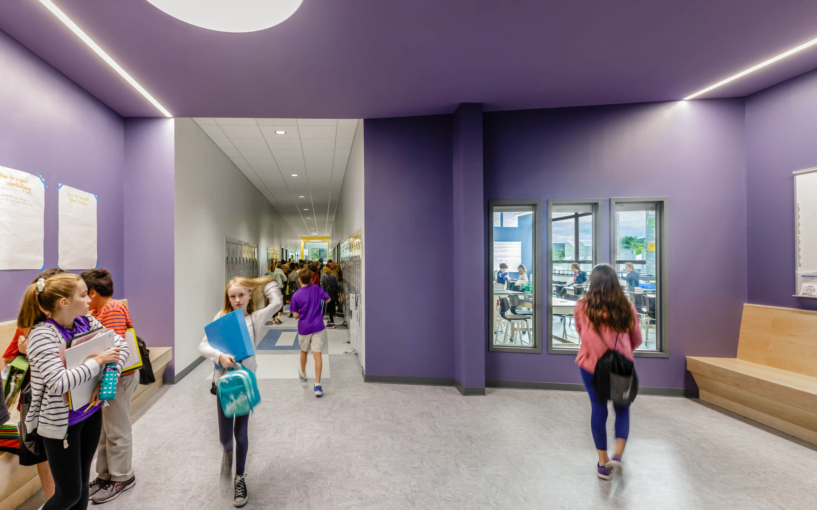Students in corridor and purple breakout space, with views into adjacent classroom.