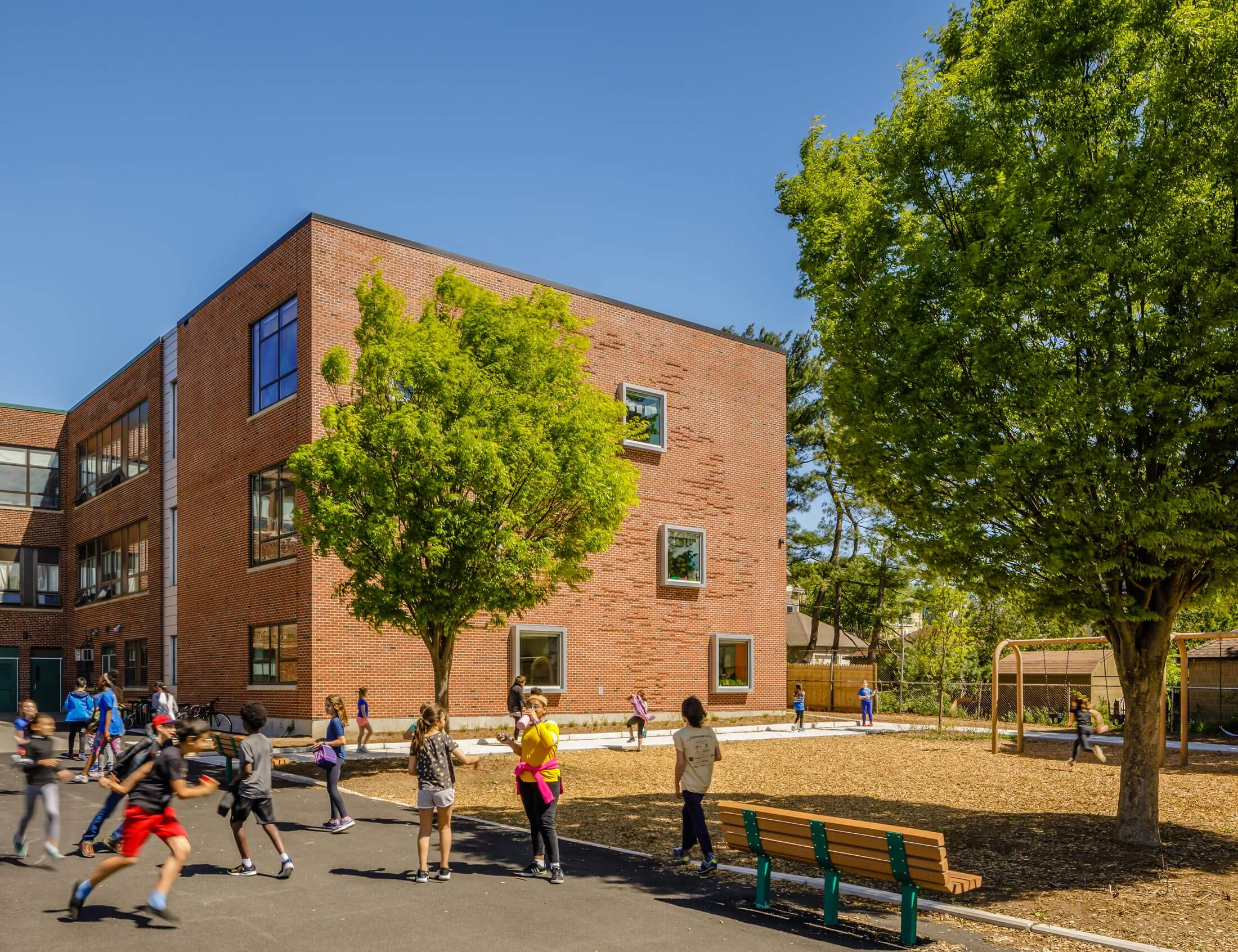 Students running on the pavement in front of the addition to the Hardy School.
