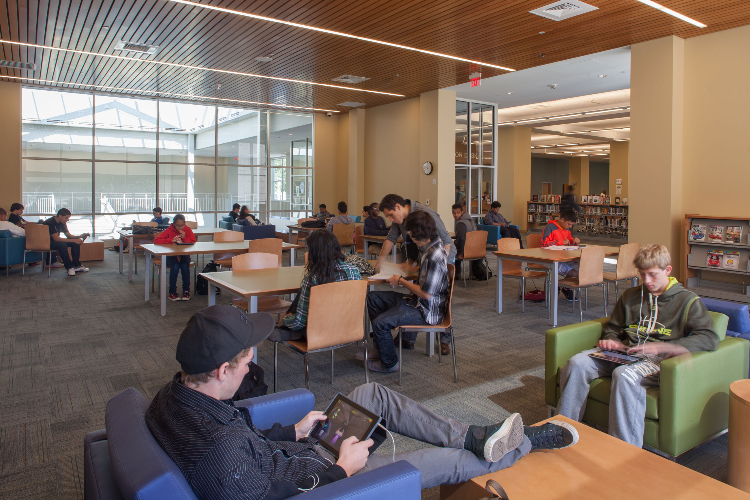 Students studying in the library, in various seating arrangements, with floor-to-ceiling windows in the background.