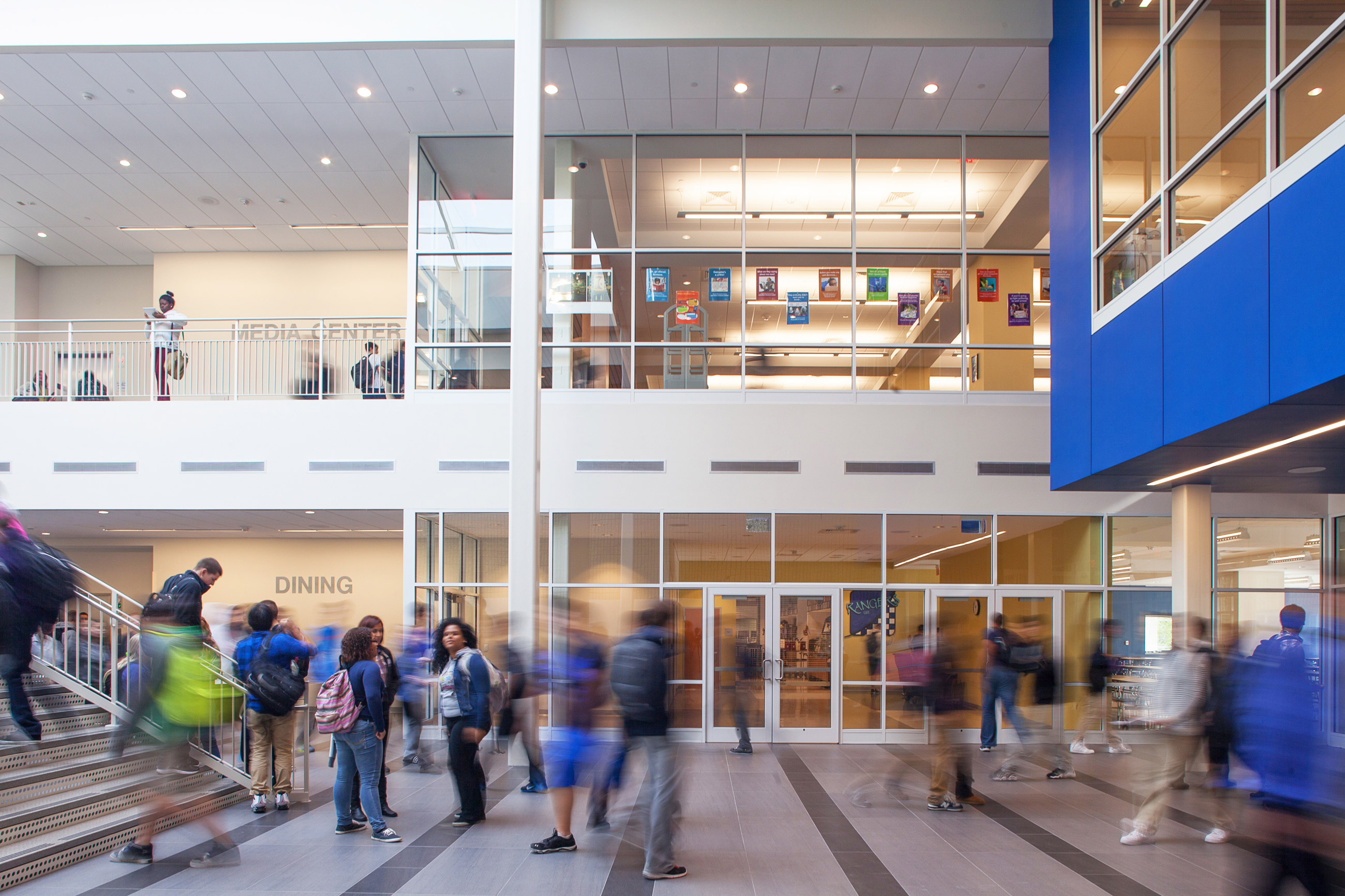 High school students walking and standing in the double-height entrance foyer of Methuen High School, in front of the dining area and the media center.
