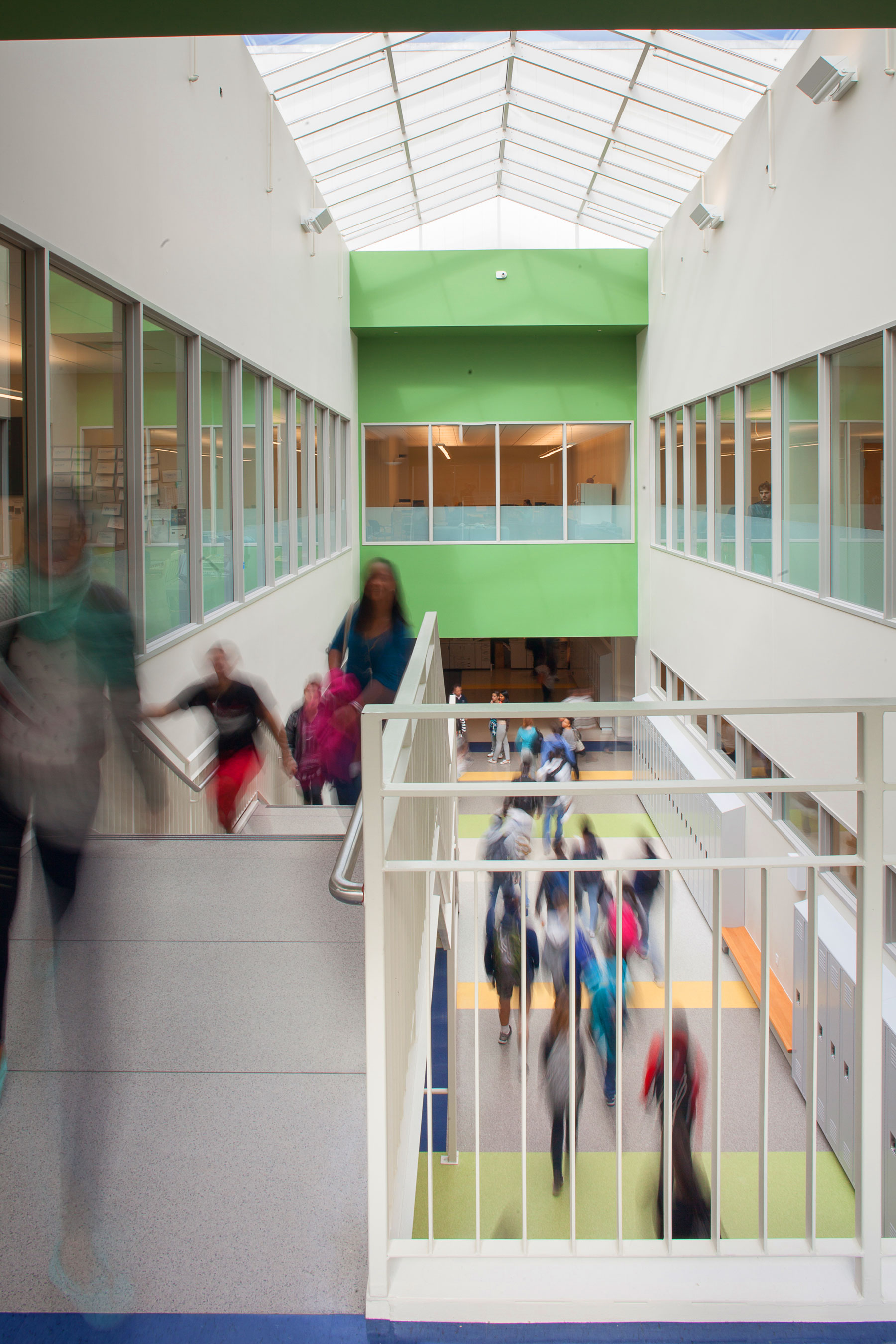 View down onto a hallway and stairs marked by green and white floors and walls under a skylight with students walking.