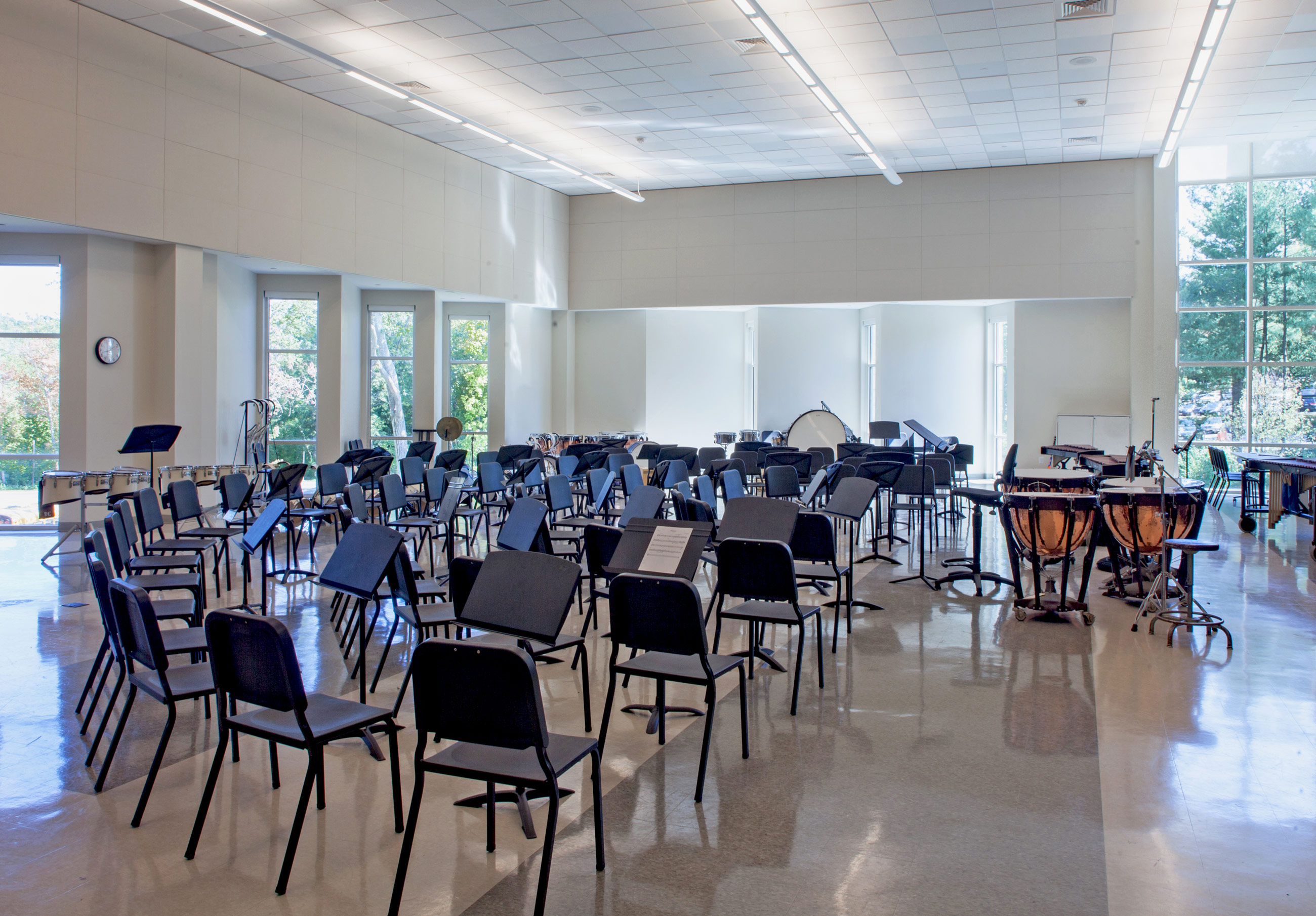 Bright, light-filled band room, with black chairs and musical equipment arranged in a semi-circle.