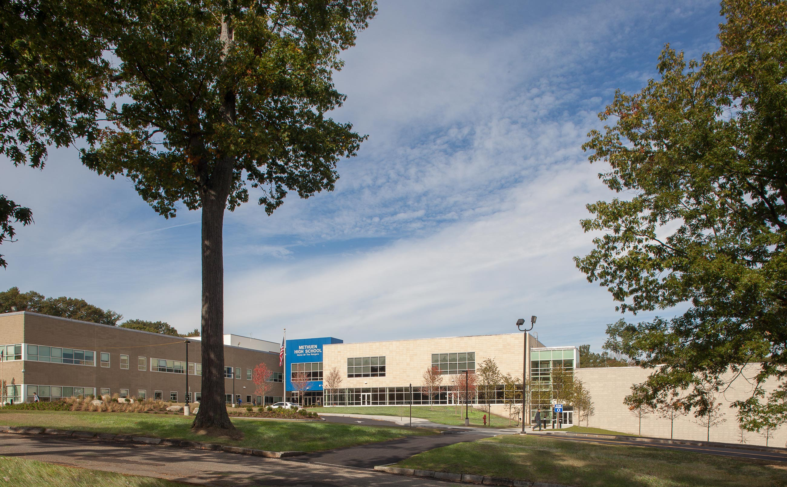 Exterior view of Methuen High Schools, with it's blue entrance visible in the background, and trees and landscaping in the foreground.