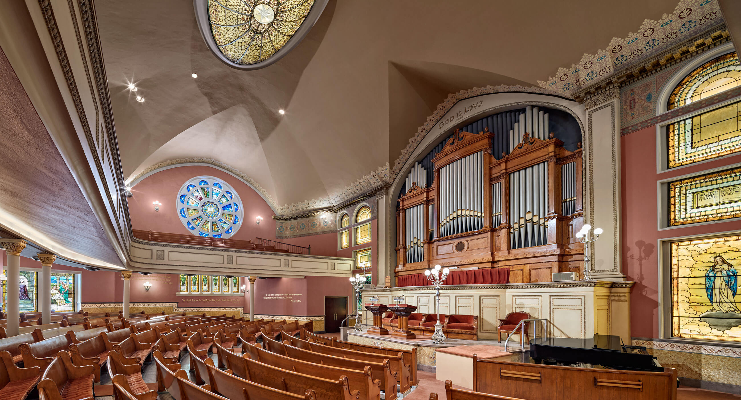 The Mother Church's interior, featuring an organ, curved pews, stained glass, rose windows and an alter, with pink walls.