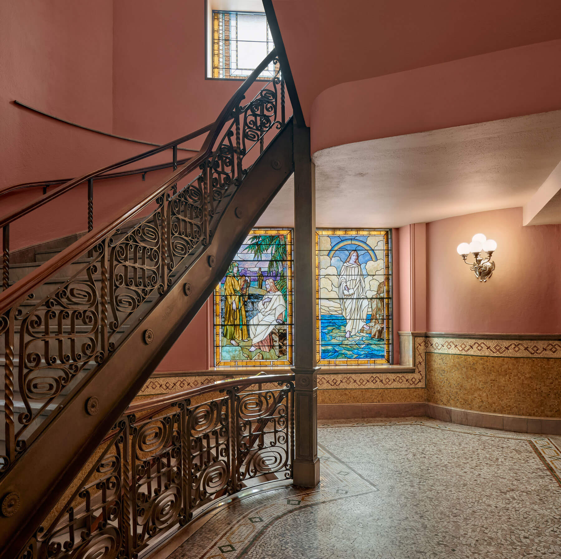 Detailed iron staircase to the right of restored stained glass windows and golden yellow mosaic details and floors.