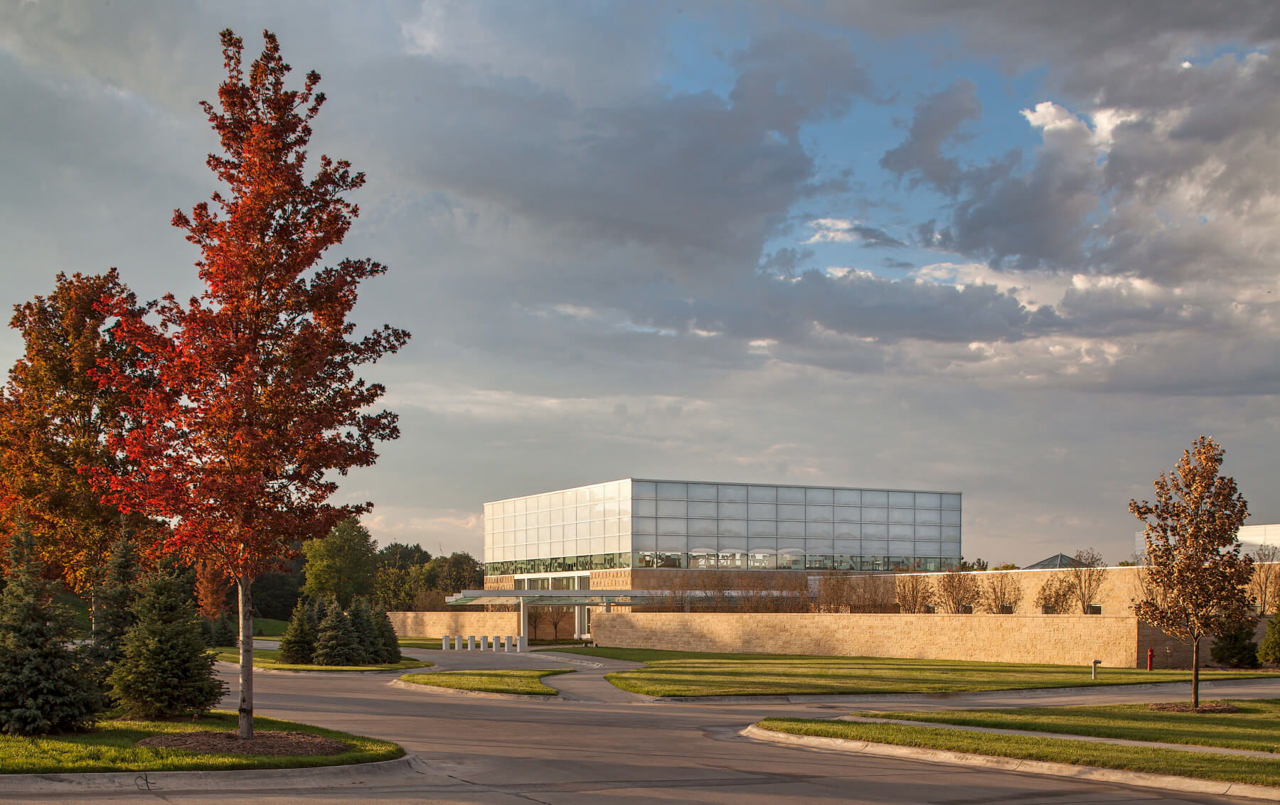 Exterior of view of Temple Israel in a golden fall light, with red trees to the left of the foreground.