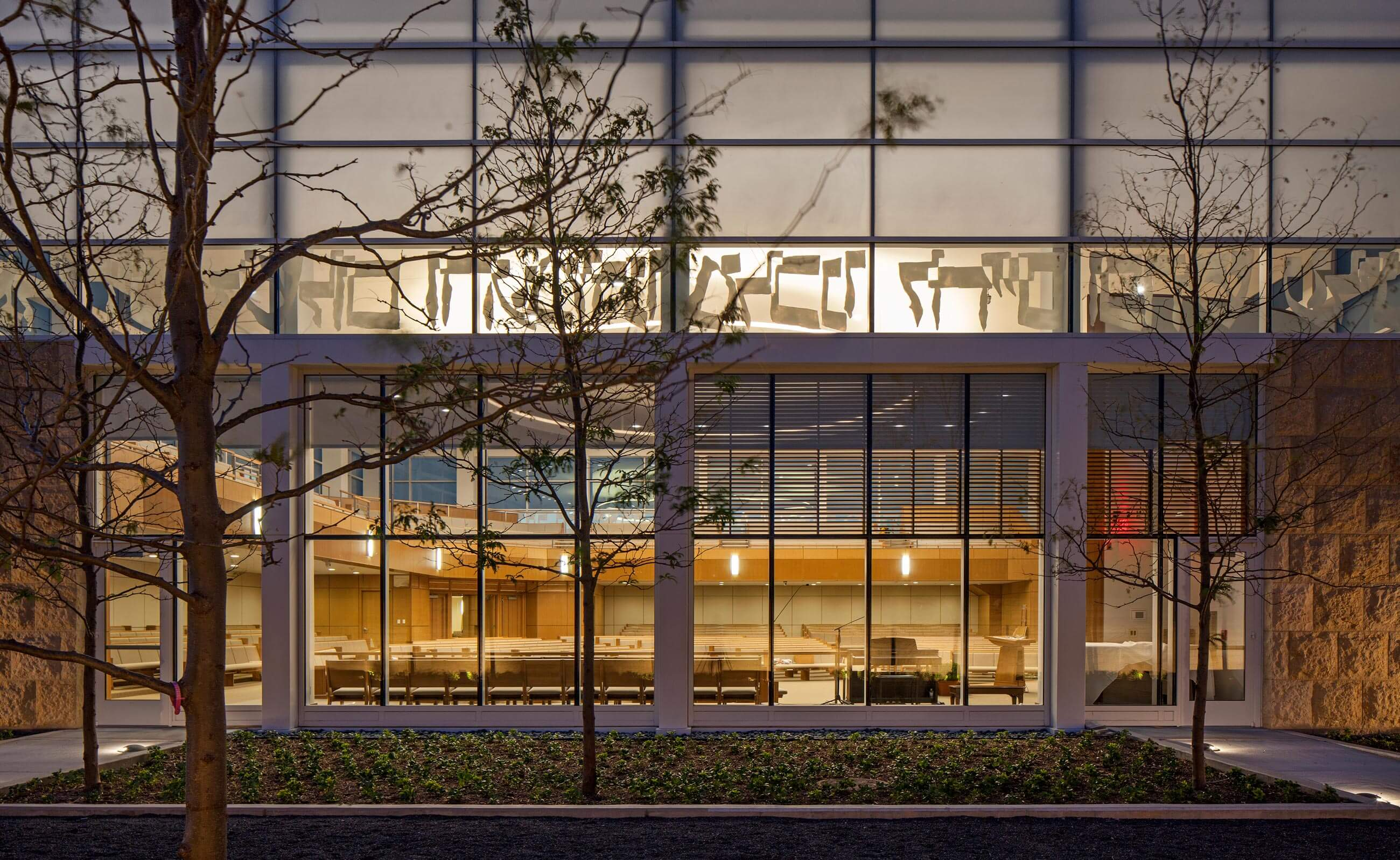 View from the courtyard into the sanctuary at night, with trees in the foreground, and Hebrew lettering at the separation between frosted and clear glass.