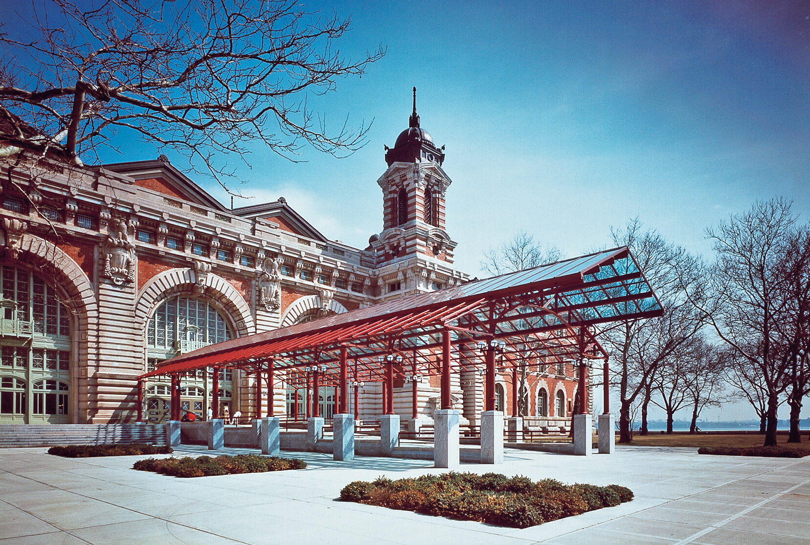 Entrance to Ellis Island museum with long perpendicular glass and steal overhang.