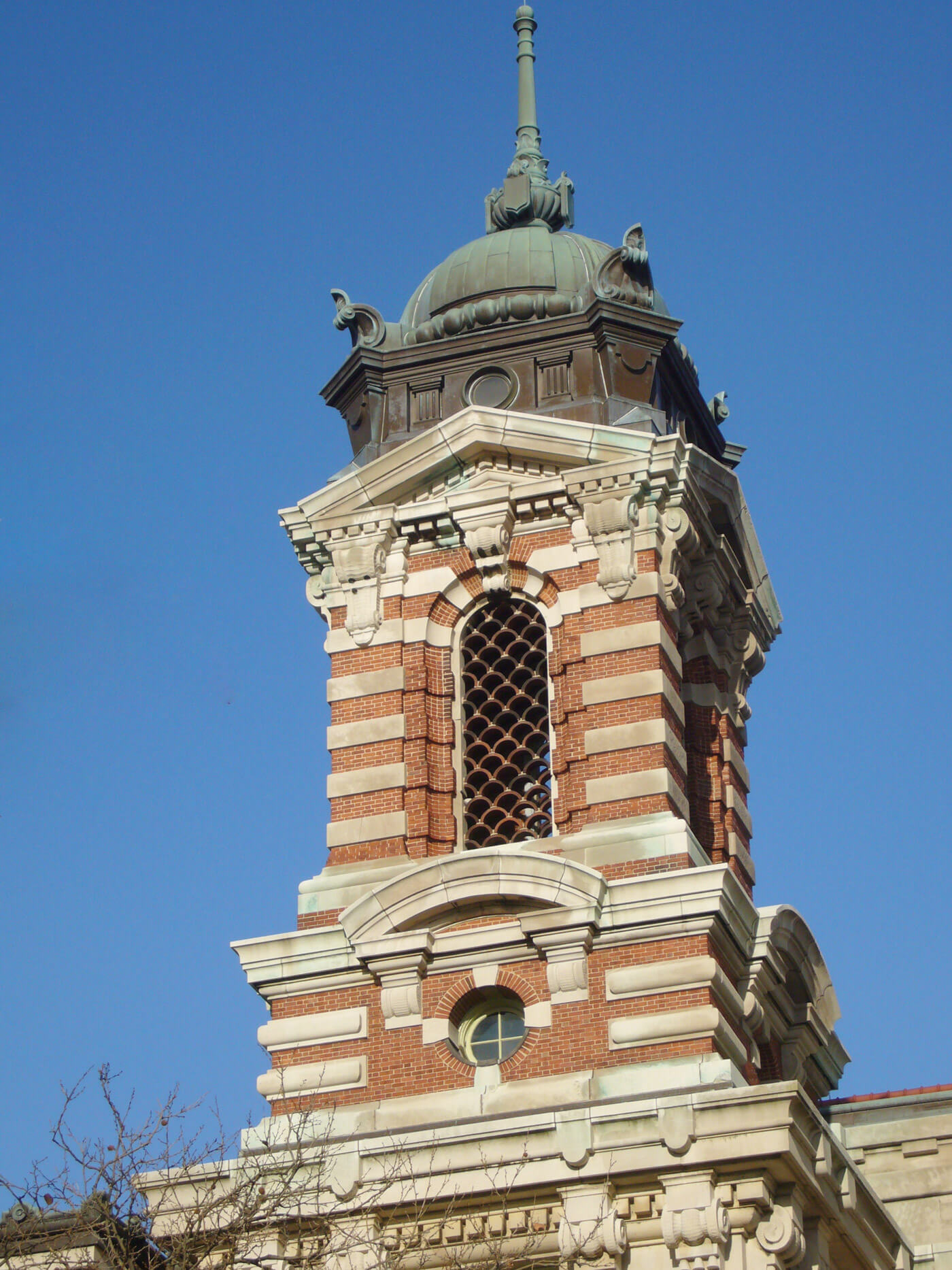 Brick and stone striped detailing on Ellis Island tower with copper roof.