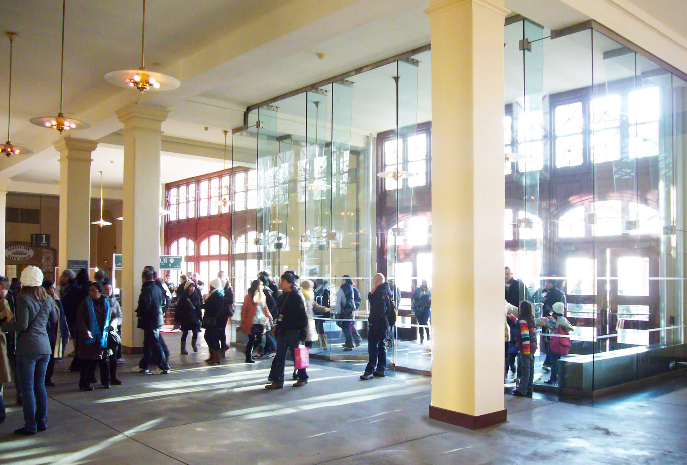 Glass entrance vestibule behind historic facade, with many people coming inside.