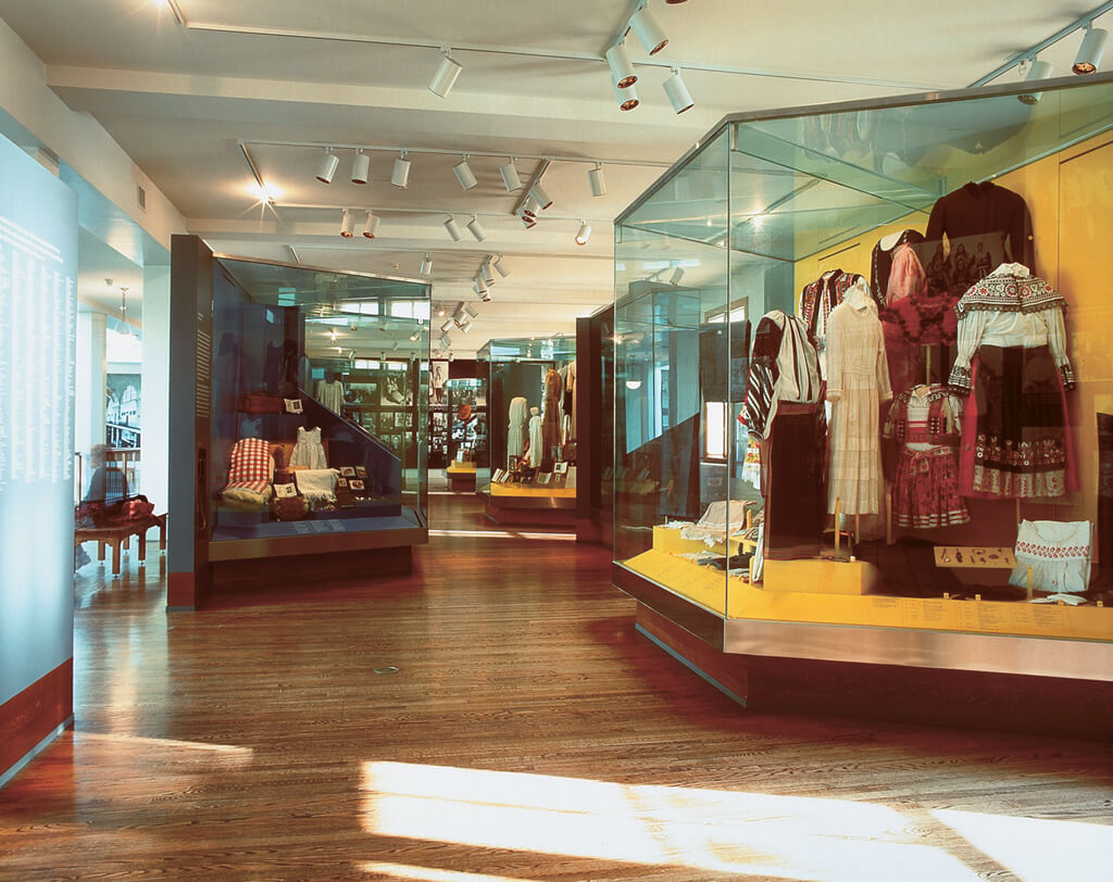 Ellis Island exhibition space with glass displays of traditional clothing.
