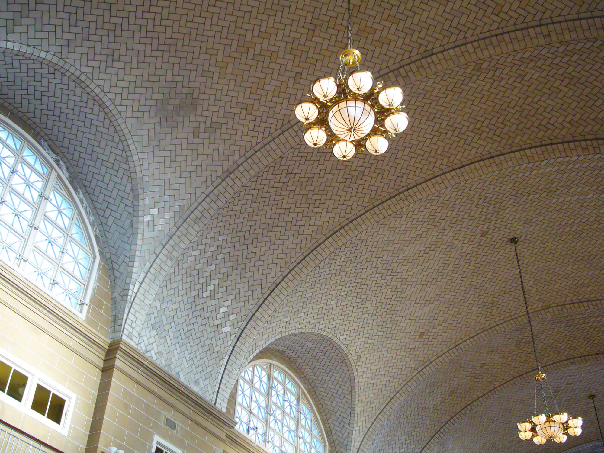 Ellis Island's Great Hall ceiling detail, with chandelier and arched windows
