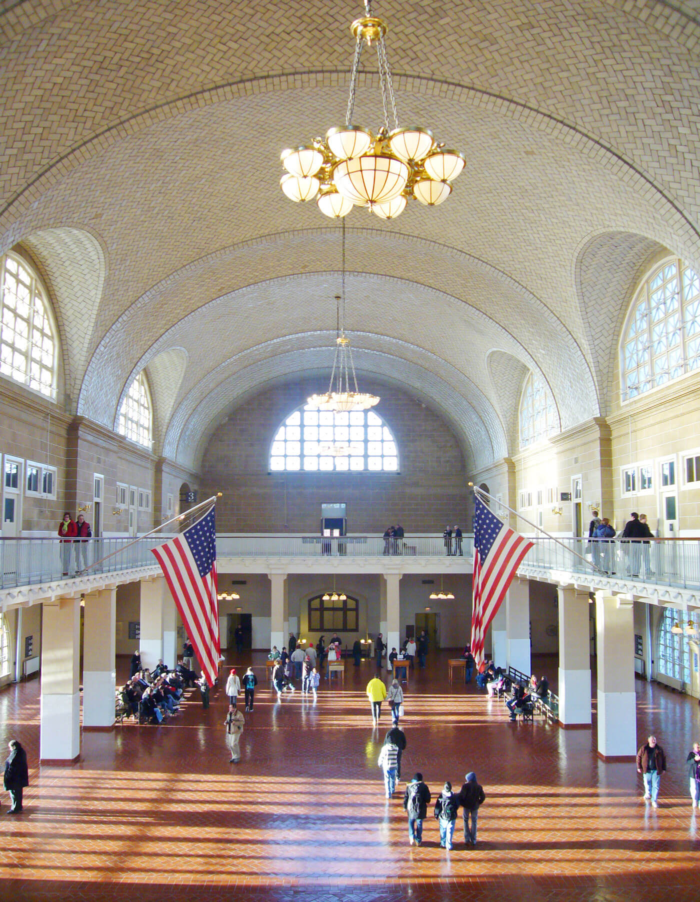 Symmetrical image of Ellis Island's Great Hall with American flag hanging on each side and people talking.