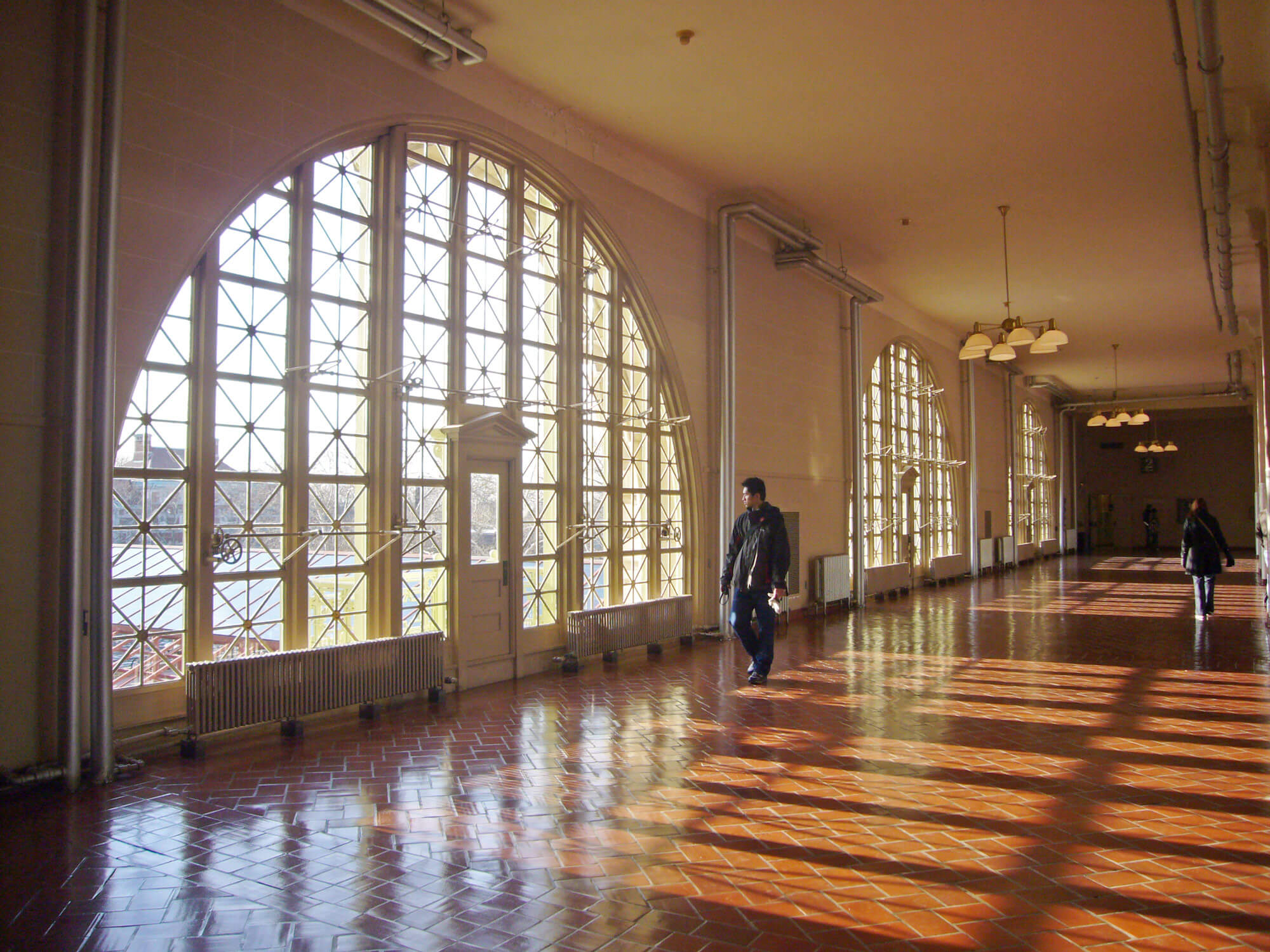 Man walking in front of large arched windows at the Ellis Island Museum of Immigration