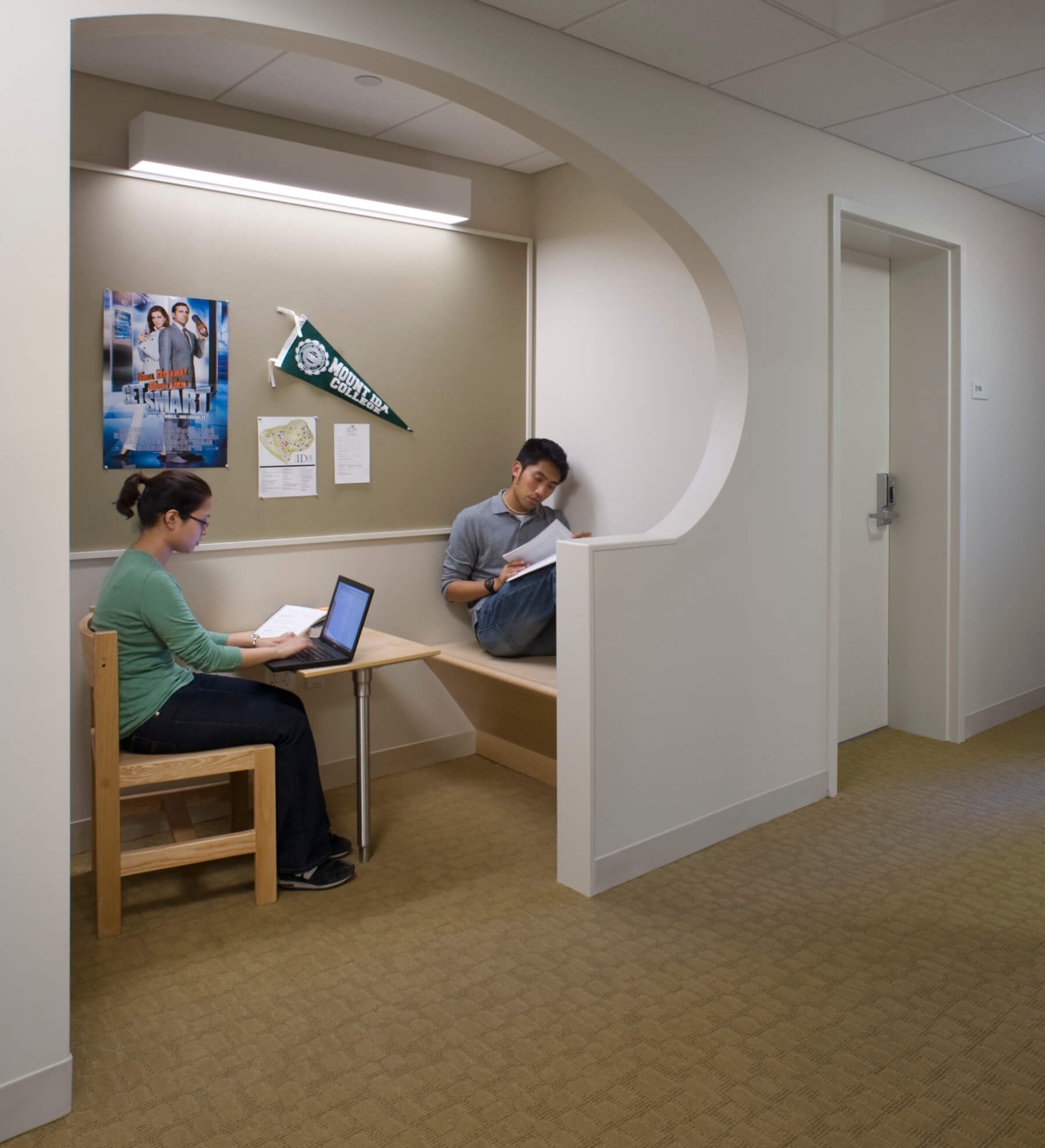 Two students in a small study nook, with posters, chairs and a desk.