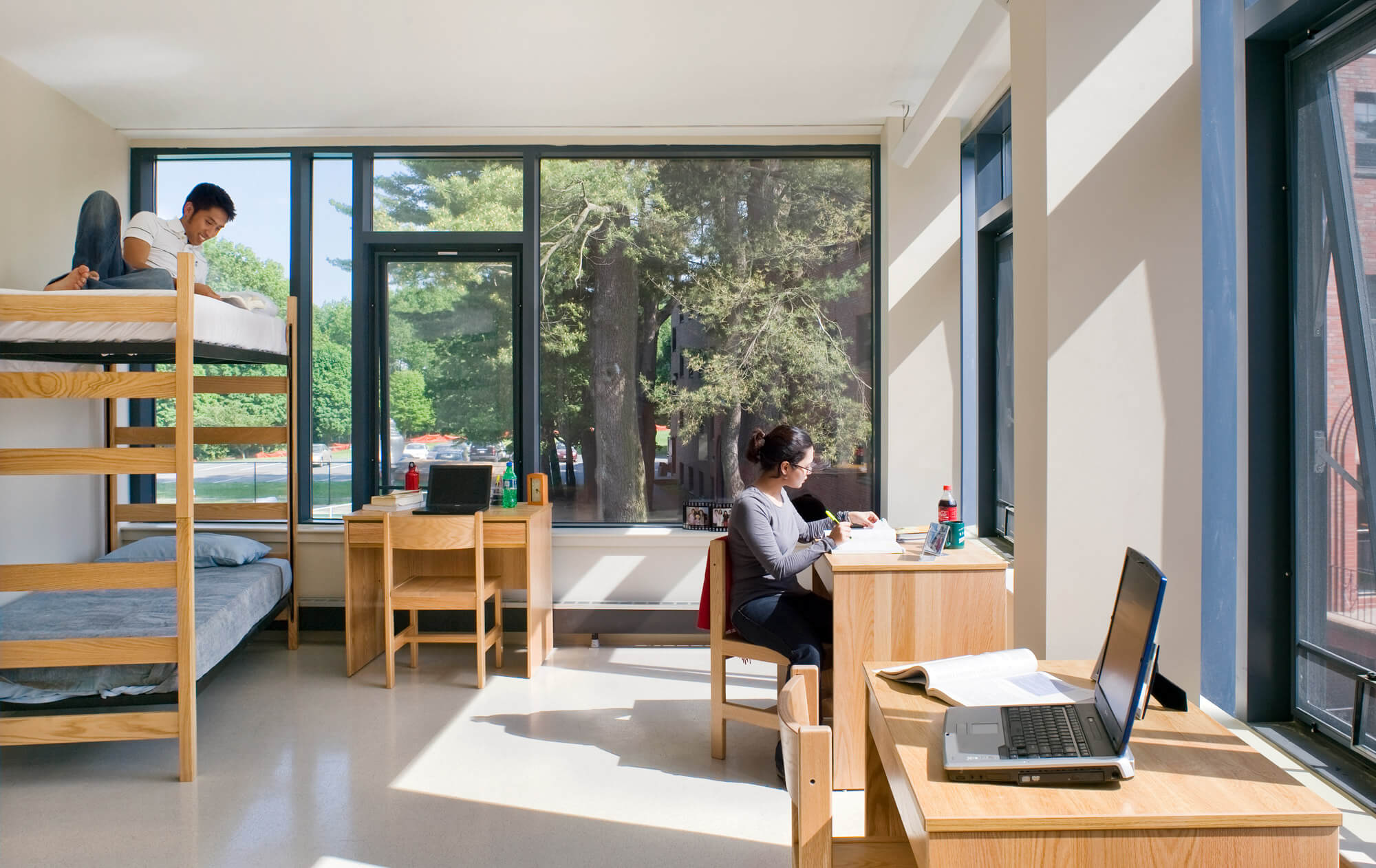 College dorm rooms with bunk beds, desks, and large windows with view onto the trees, letting in bright, natural light.