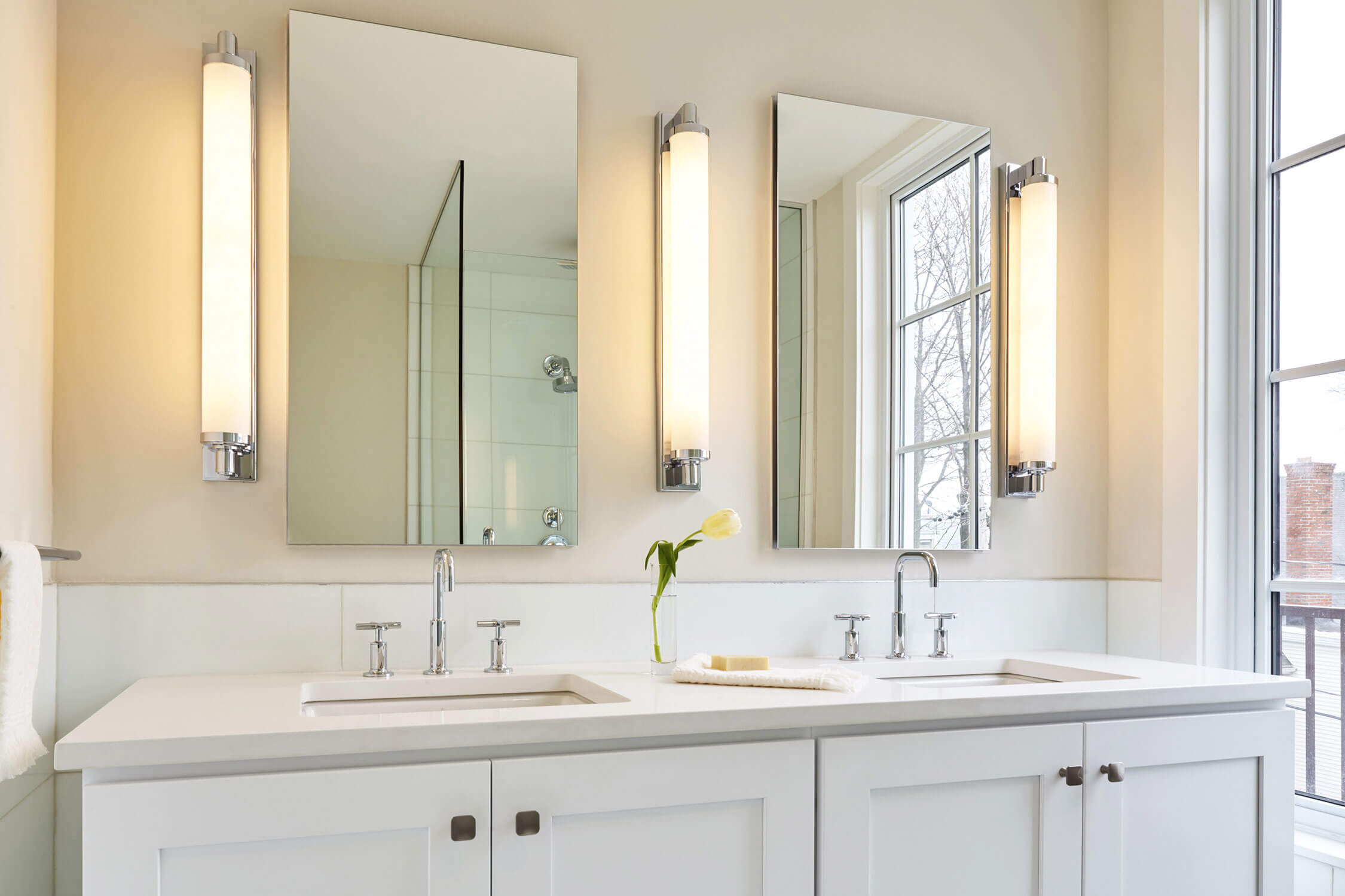 Side-by-side bathroom sinks with mirrors and three cylindrical lights between the mirrors.