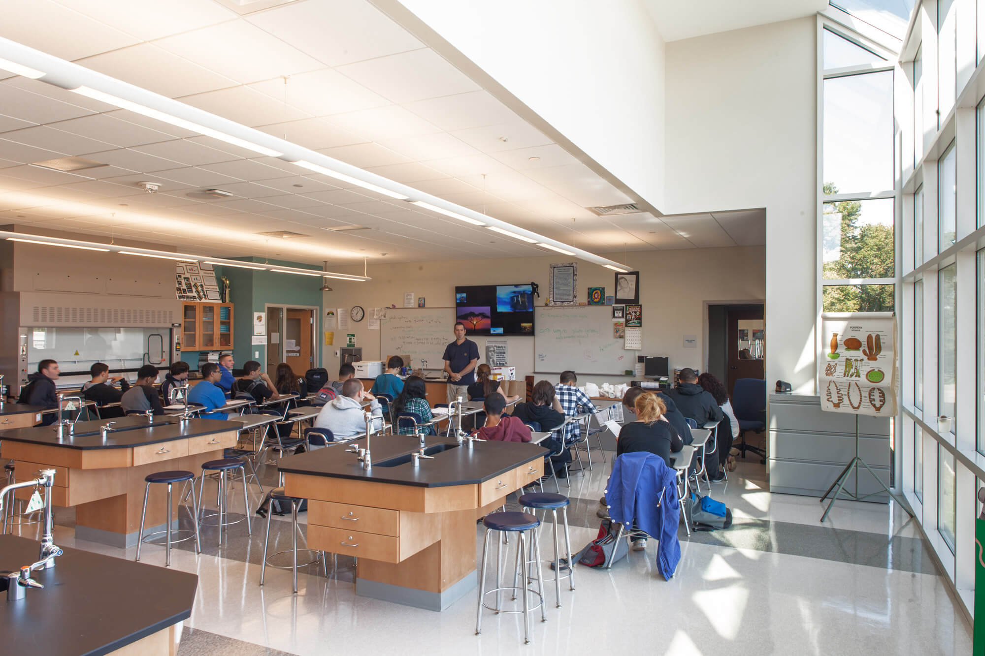 Students sitting at their desks in a science classroom with lab spaces to the left, and floor-to-ceiling windows to the right, letting in natural light.