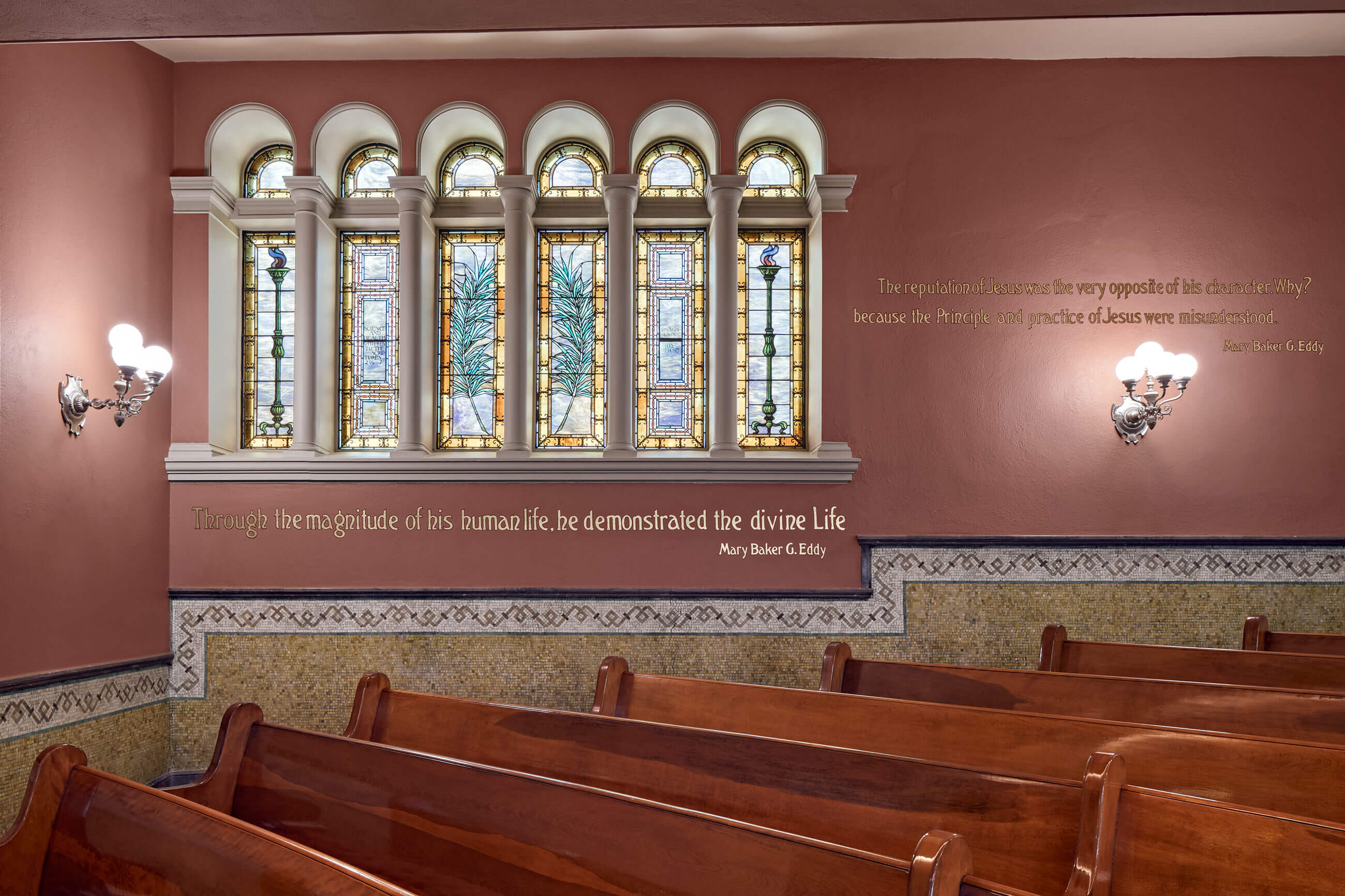 Detailed shot of restored, arched stained glass windows, with a quotation from Mary Baker G. Eddy in gold lettering and restored mosaics below.