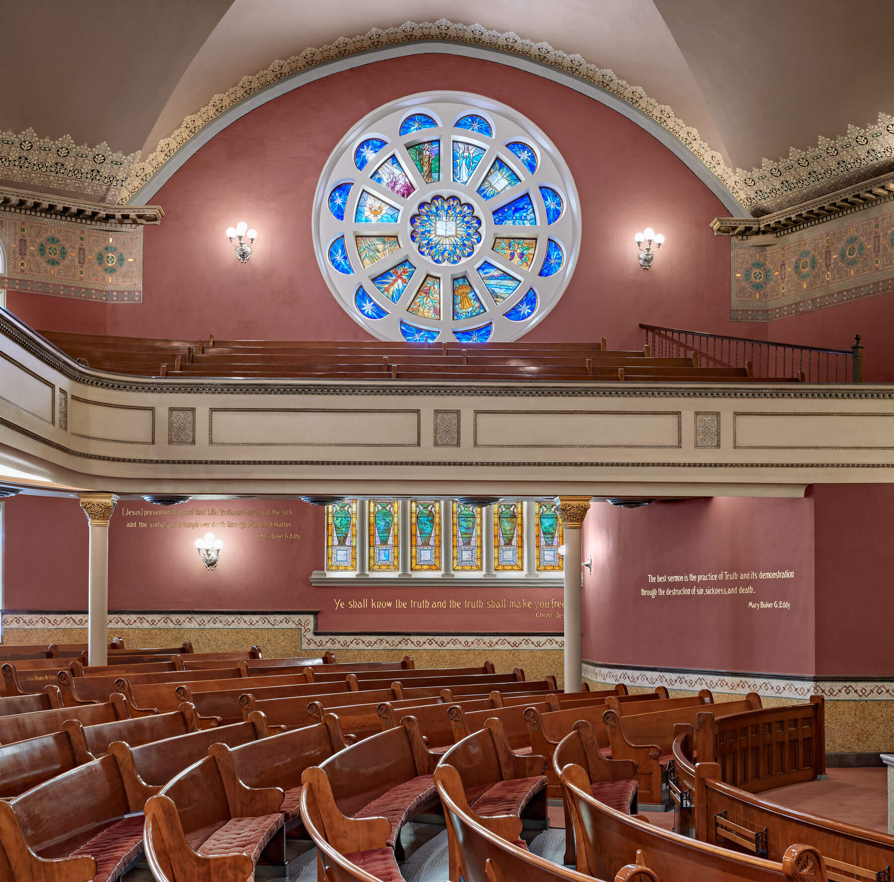 Curved pews  with a detailed rose window above the second floor balcony, on a pink background.
