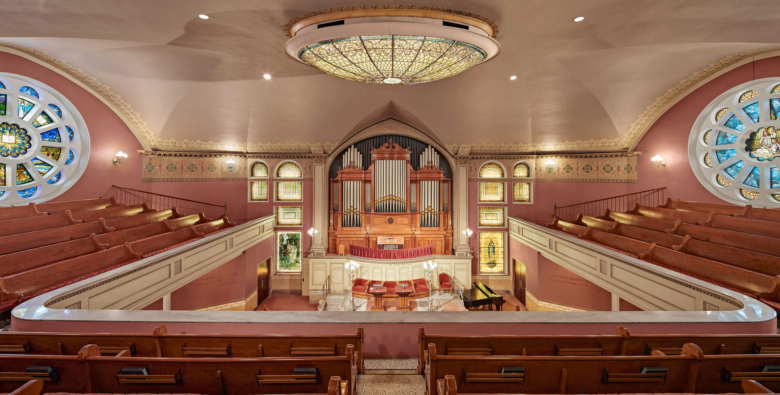 Panoramic view of the altar, organ, pews and balcony, framed by two rose windows.