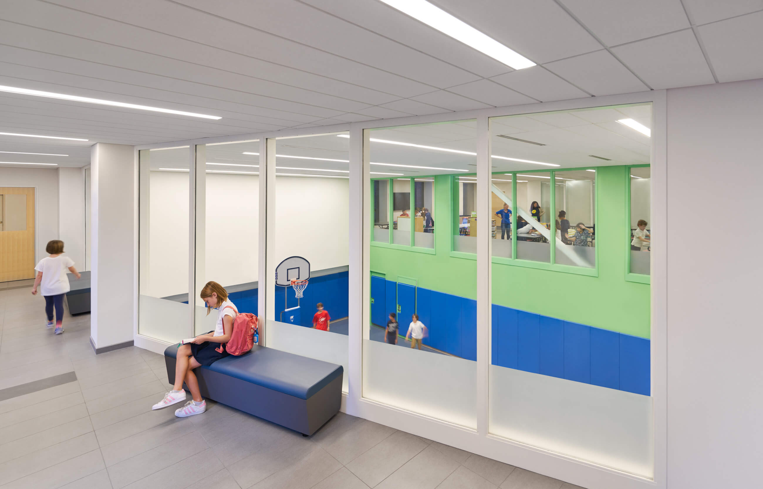 Girl sitting on bench in entry hallway, with windows overlooking the green and blue gym below.