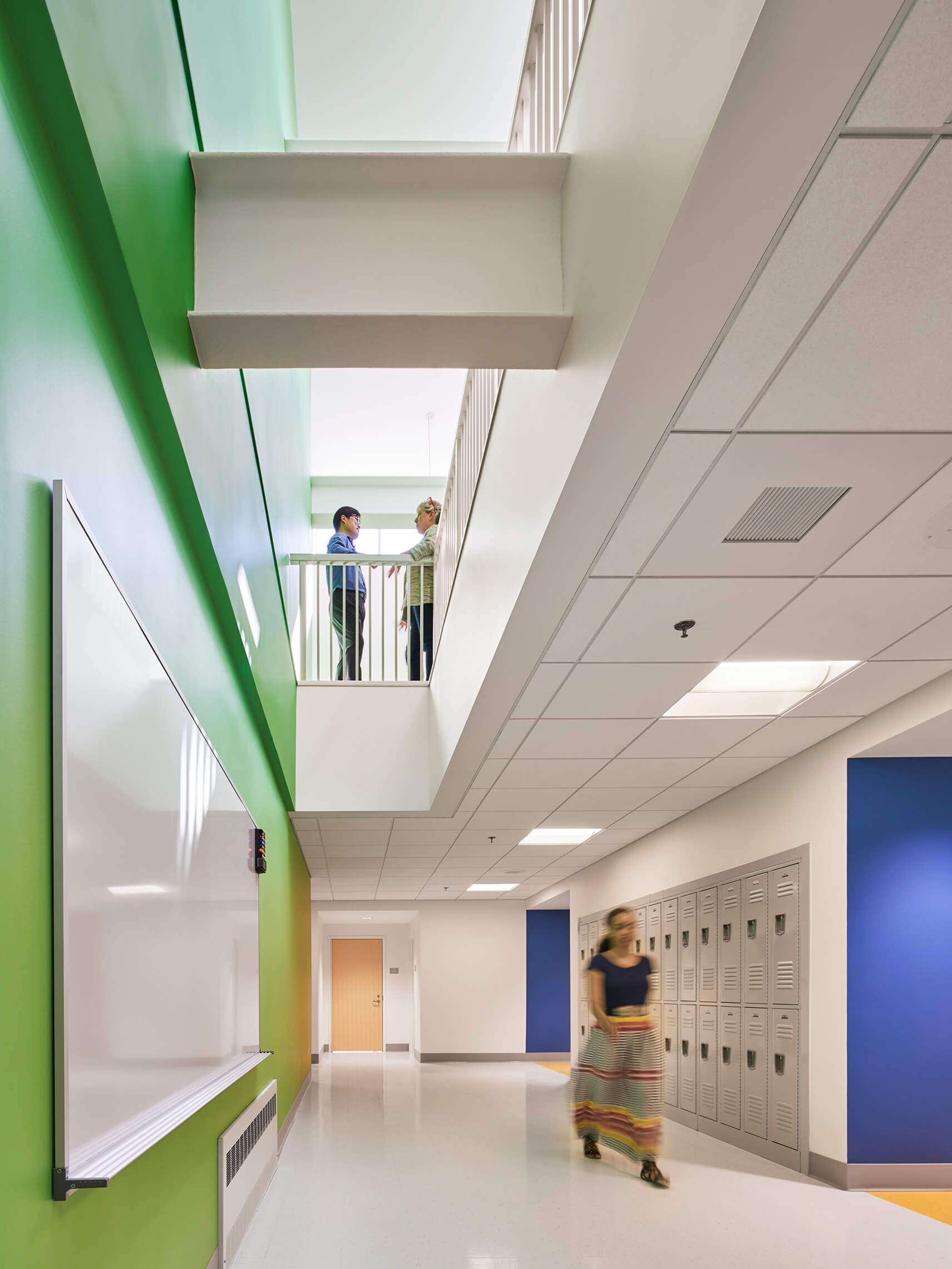 Woman walking down green and blue hallway with lockers, a whiteboard, and people talking on the second floor.