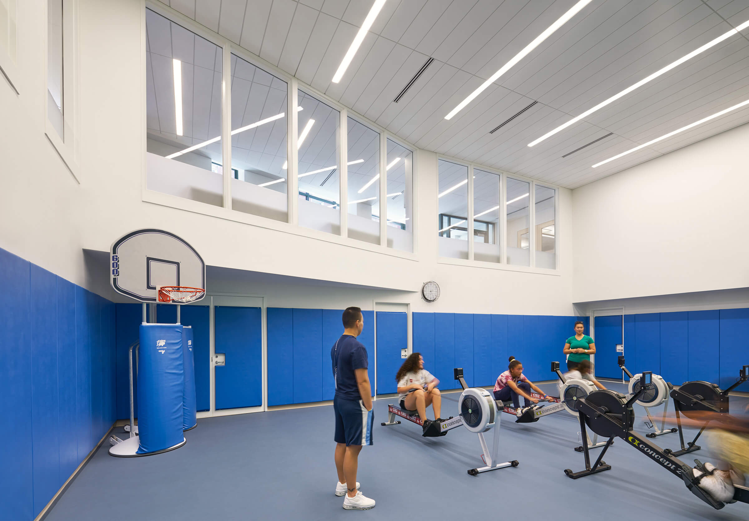 Basketball hoop to the left of students practicing on stationary rowing machines on a royal blue background and windows near the ceiling..