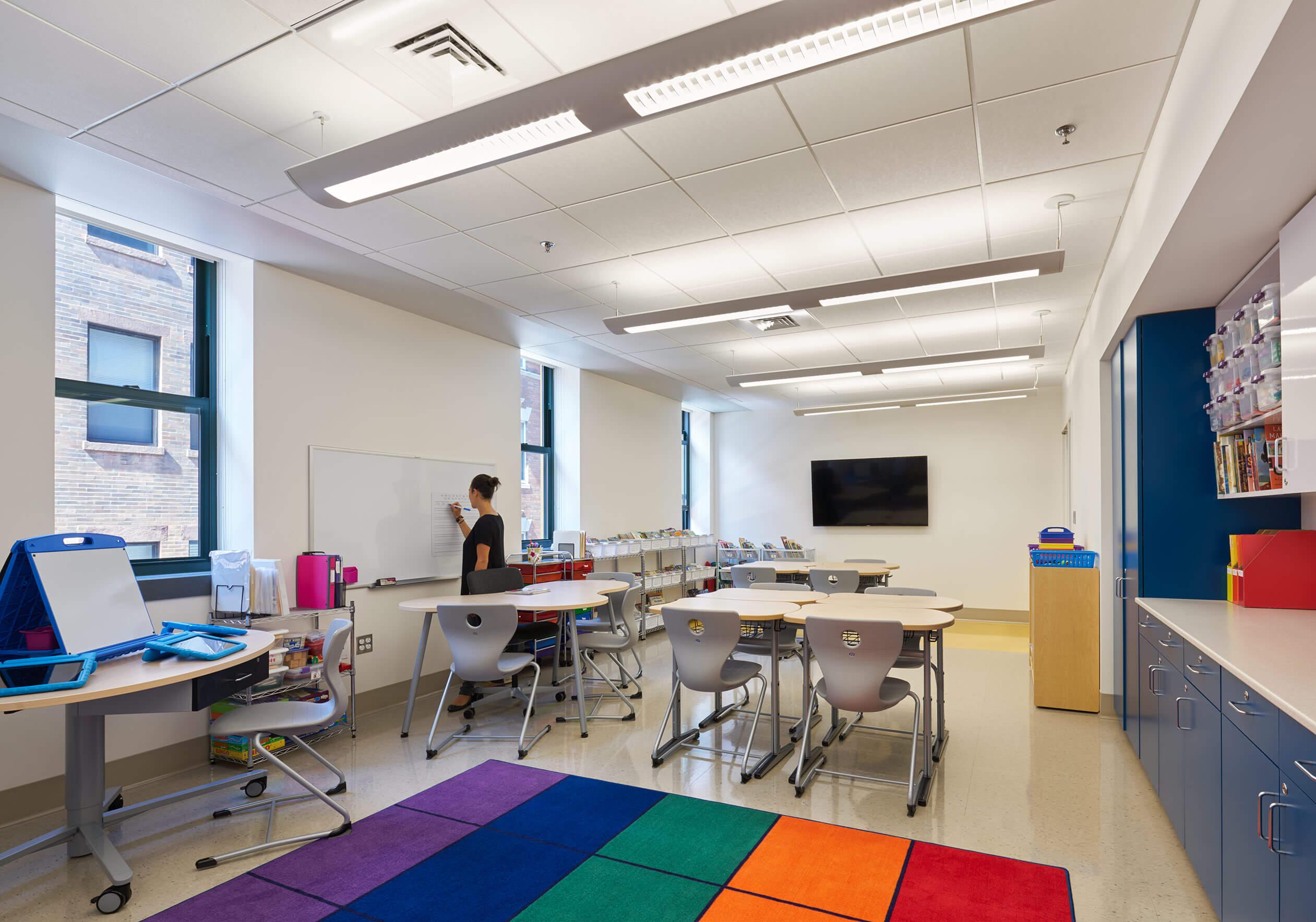 Rainbow rug, with desks in classroom teacher writing on whiteboard.