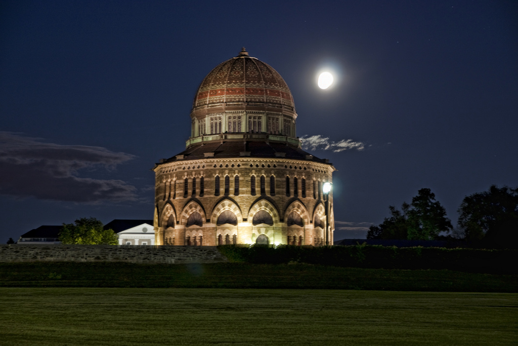 Nott Memorial at night, with the moon and the building's lighting emphasizing its cylindrical shape and and beautifully detailed dome.