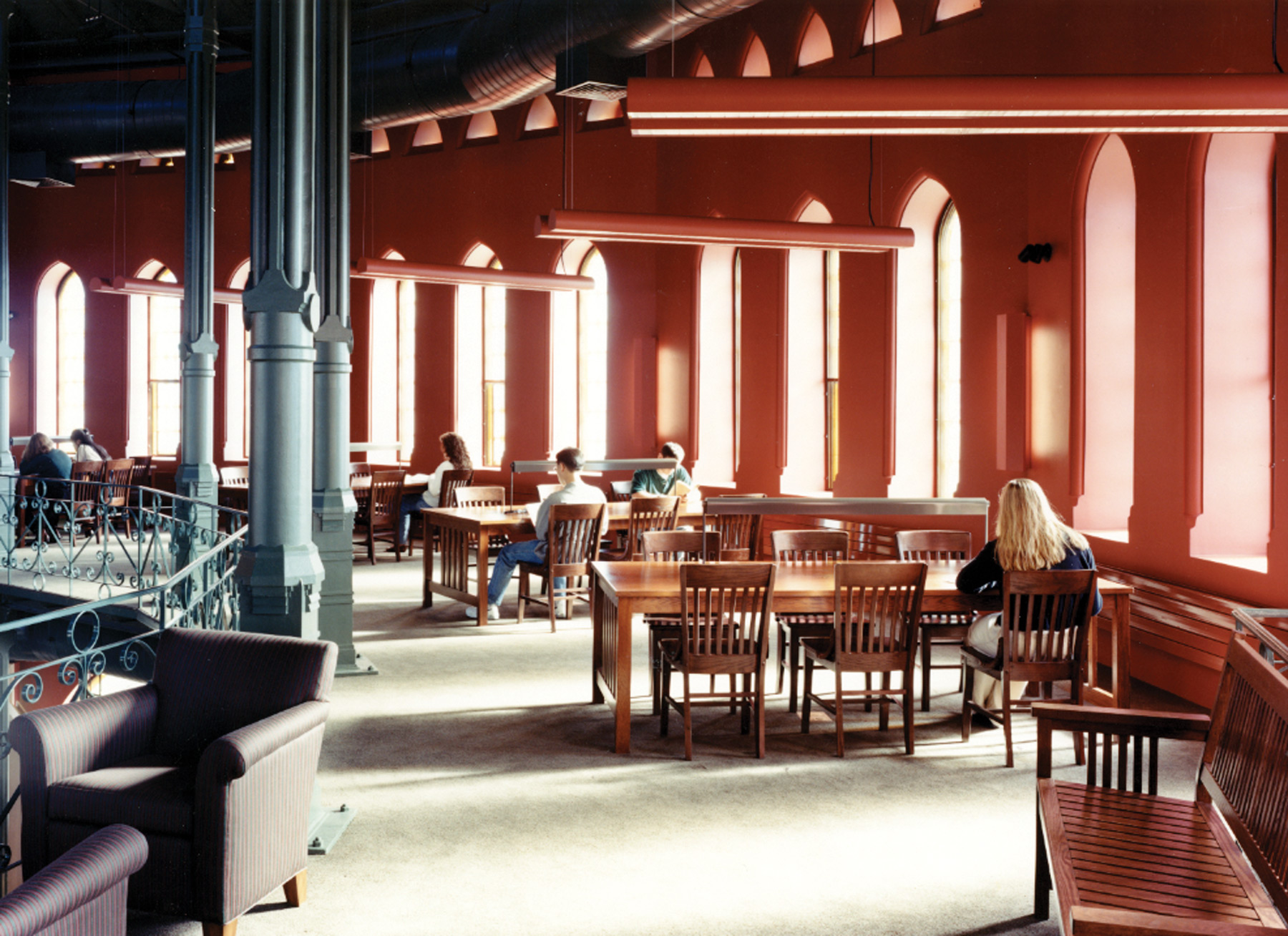 Students studying at tables on one of the elevated levels of the Nott Memorial, with abundant daylight streaming in through arched windows.