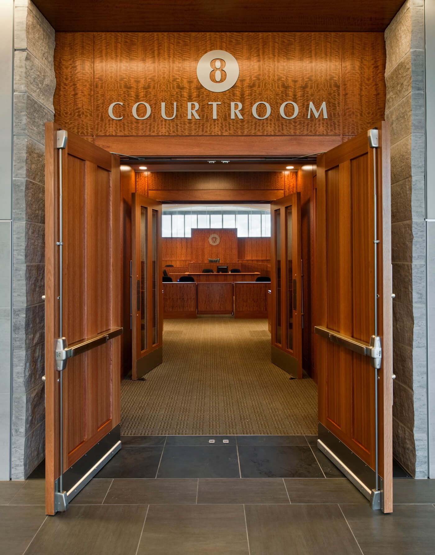 Large courtroom 8 entrance with open door, framed by dark, yet warm wood finishes.